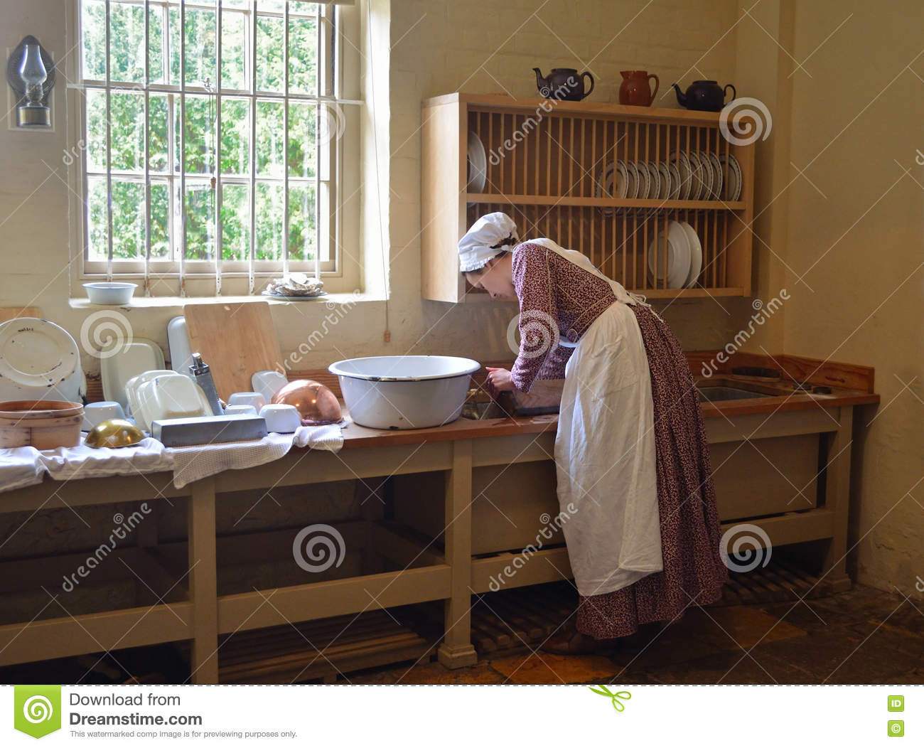 Young Woman Dressed As Victoria Kitchen Maid Washing Dishes In ...