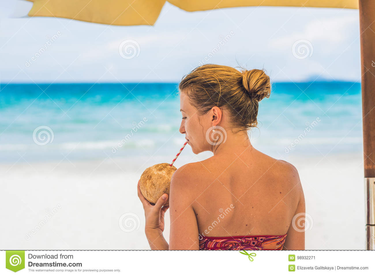 Young Woman Drinking Coconut Milk On Chaise-longue On Beach