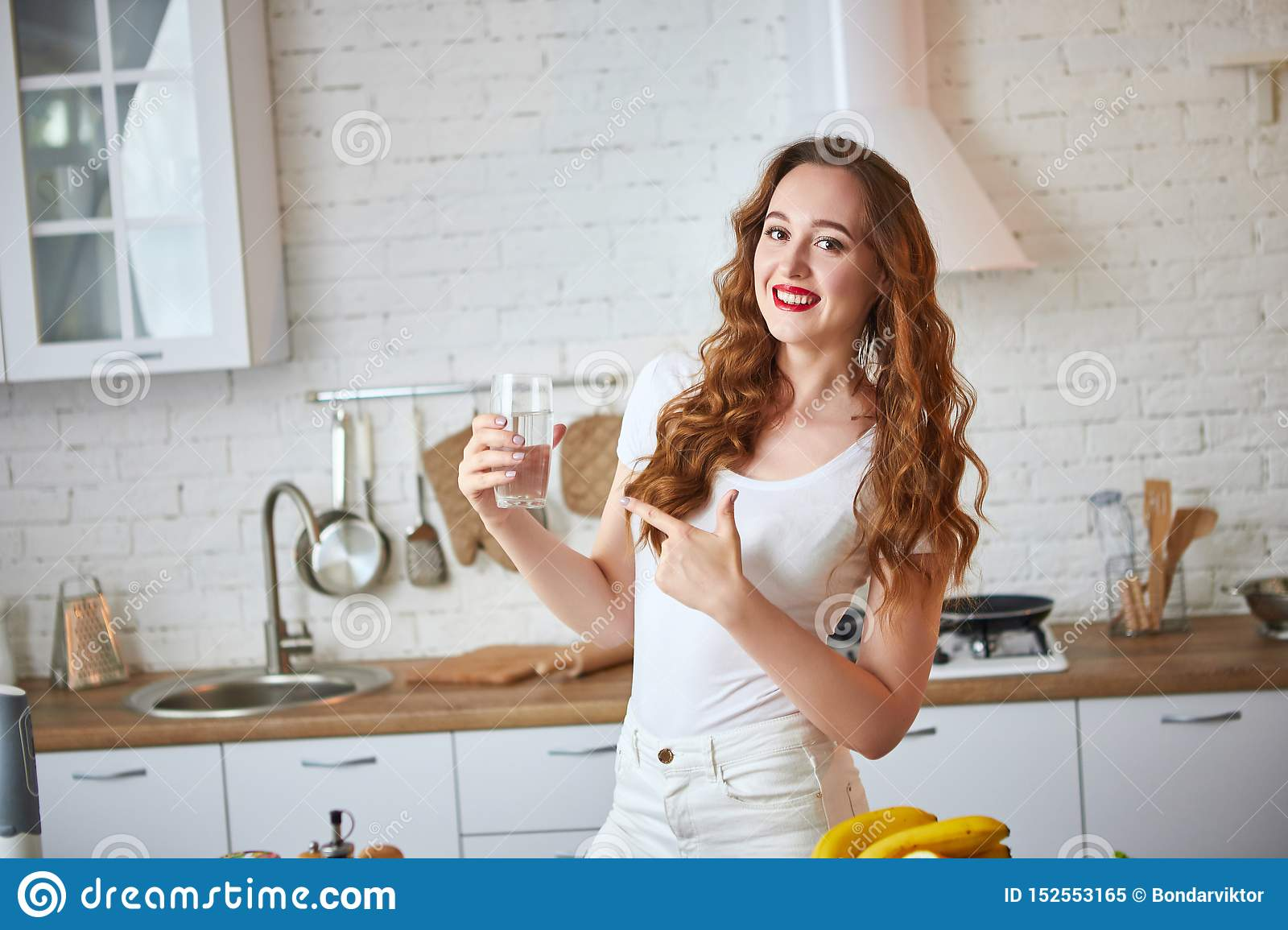 Young woman drinking fresh water from glass in the kitchen. Healthy Lifestyle and Eating. Health, Beauty, Diet Concept