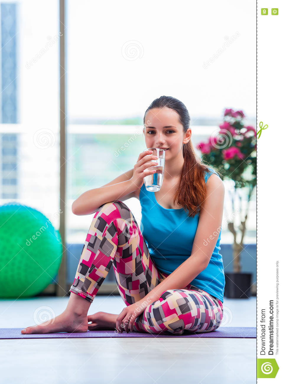 The young woman drinking water in gym health concept stock image the young woman drinking water in gym health concept sciox Gallery