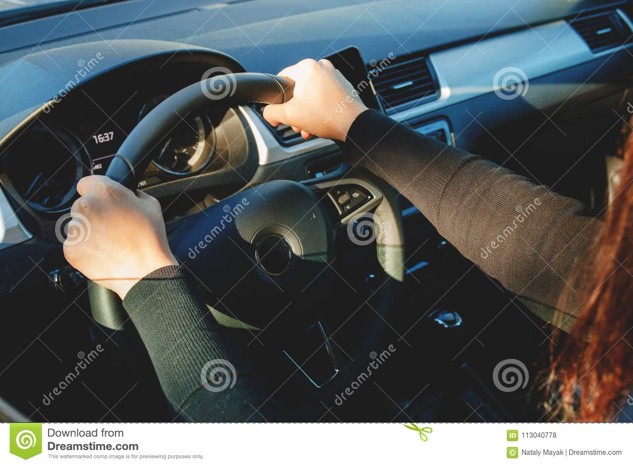 A young woman driving a car on a sunny day