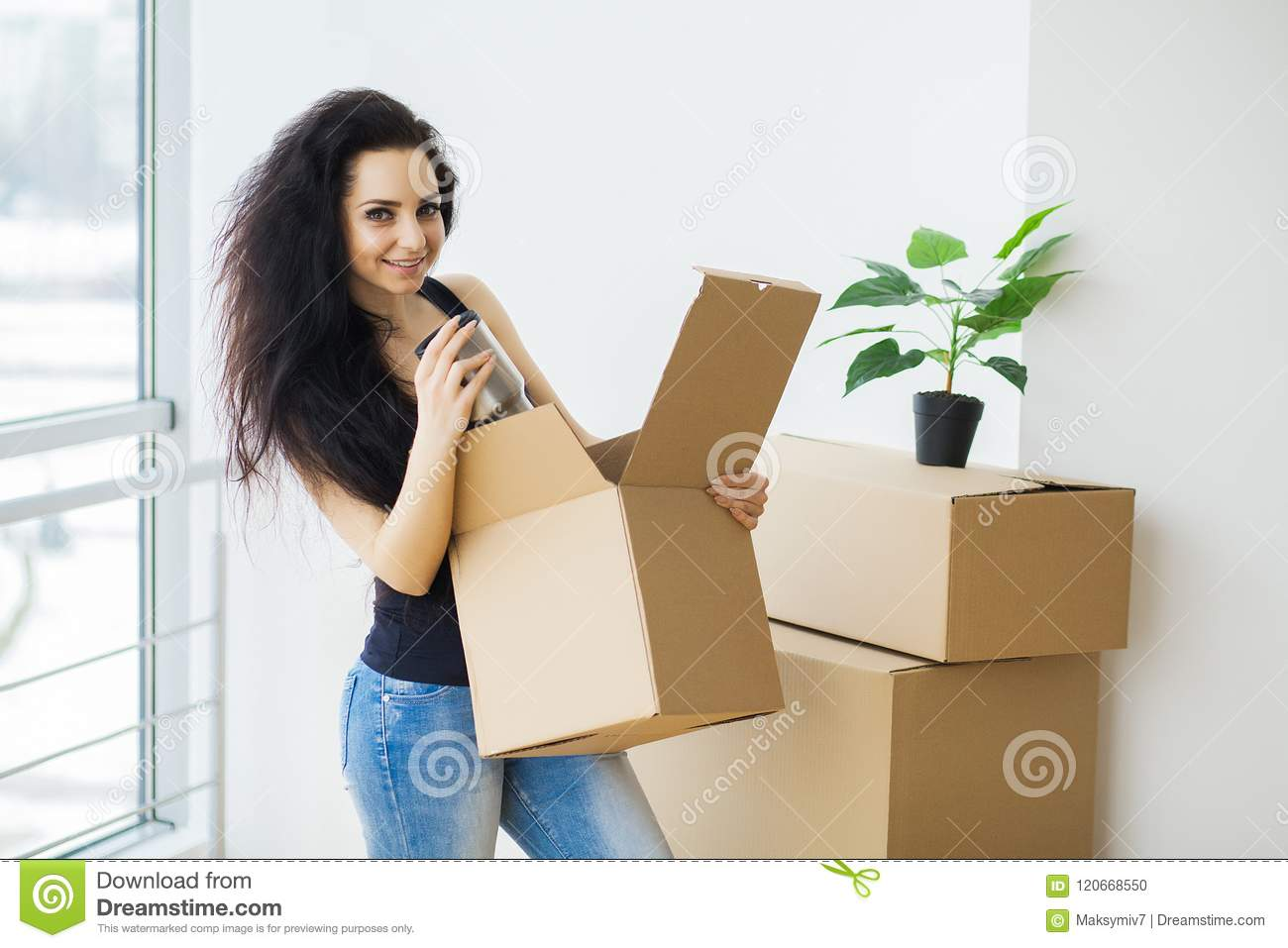 Young woman dropping cardboard box. Moving into new home