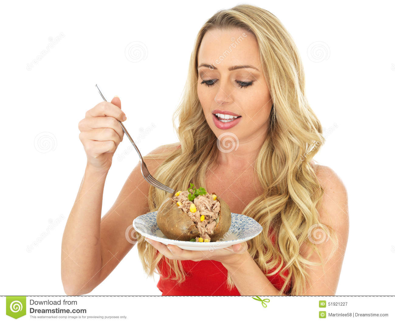 Young Woman Eating A Baked Potato With Tuna And Sweetcorn