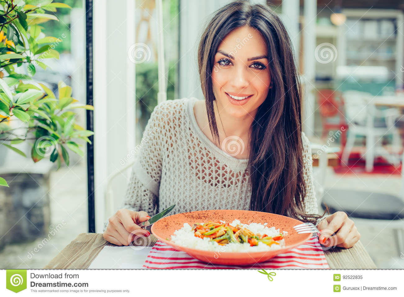 Young woman eating chinese food in a restaurant, having her lunch break