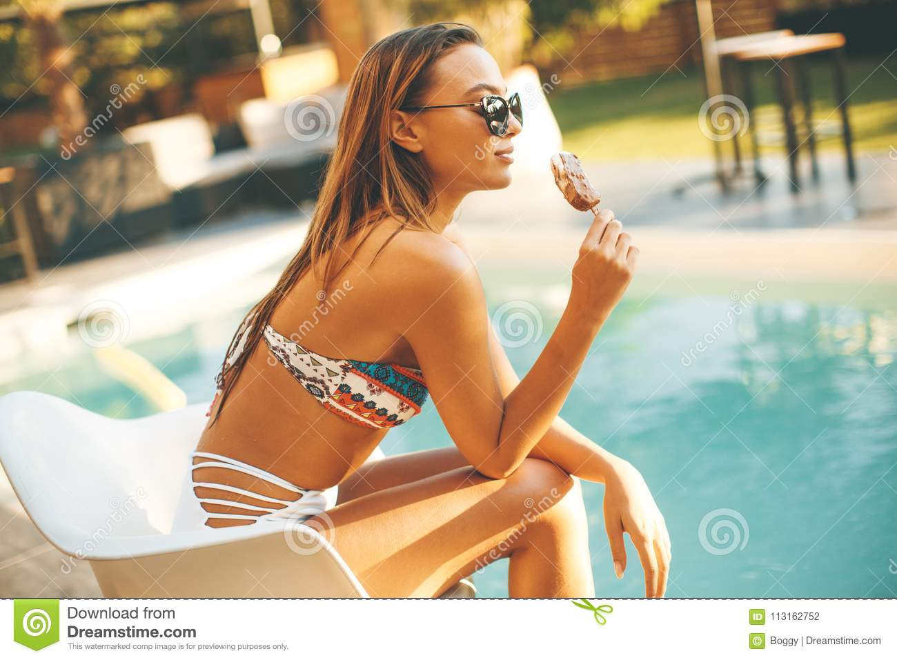 Young woman eating icecream near the swimming pool