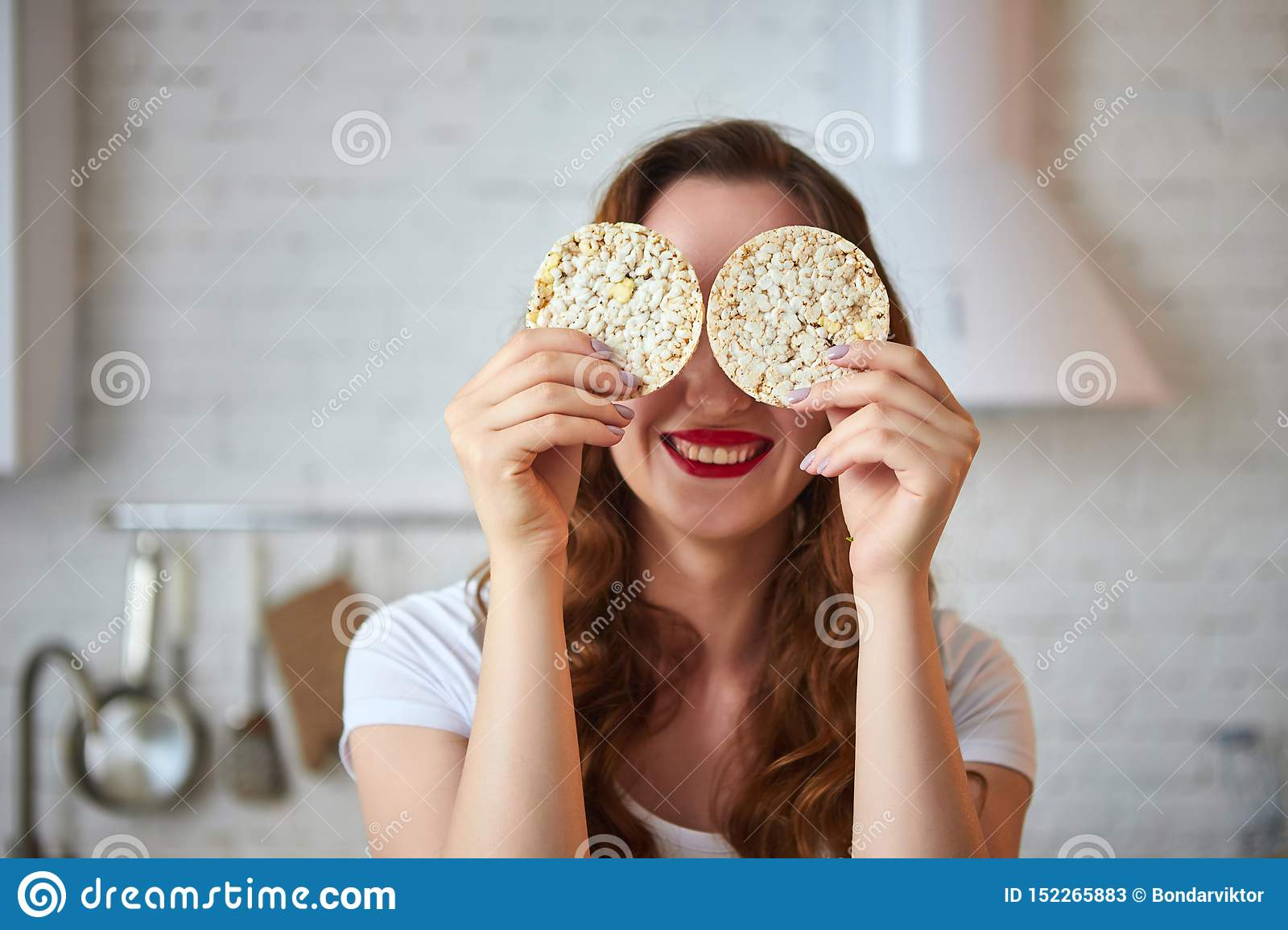 Young woman eating rye cracker crisp bread in the kitchen. Healthy Lifestyle. Health, Beauty, Diet Concept
