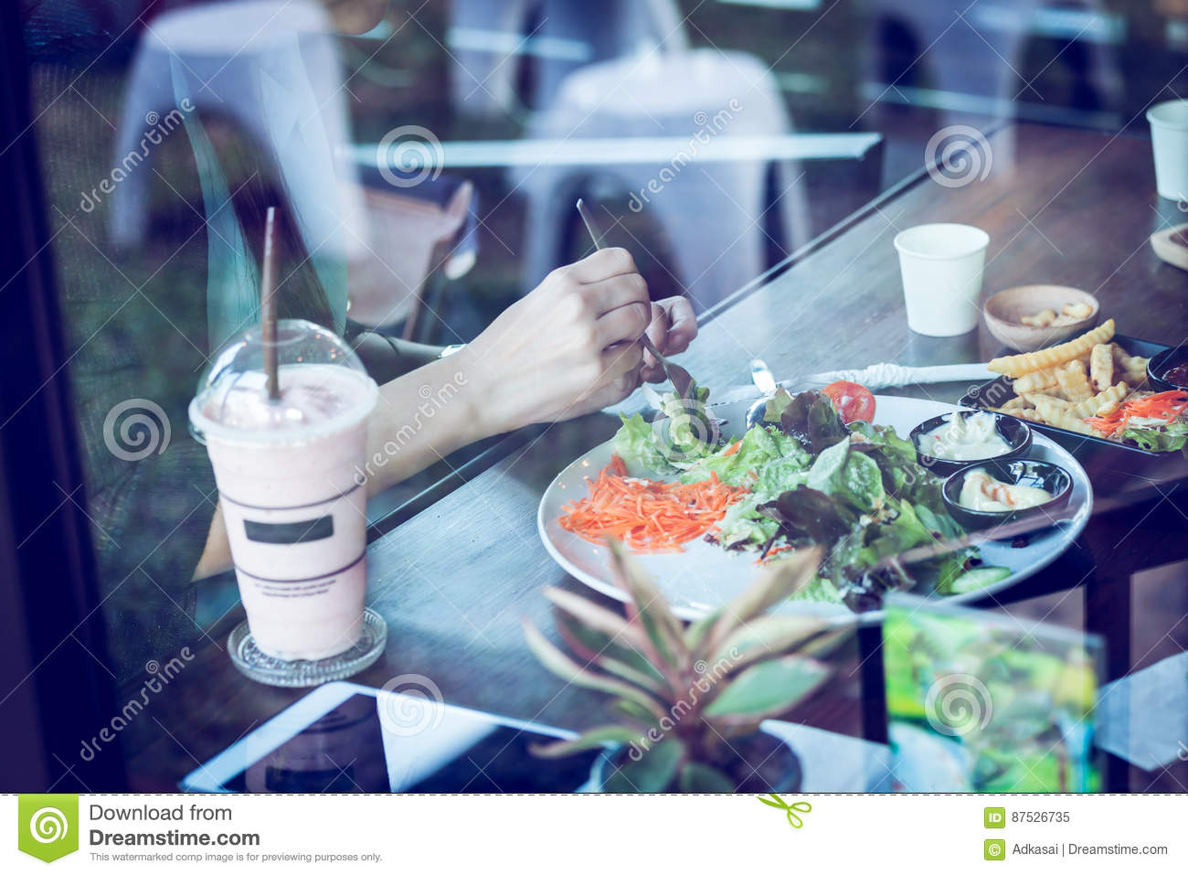 Young woman eating salad and beverage in cafe