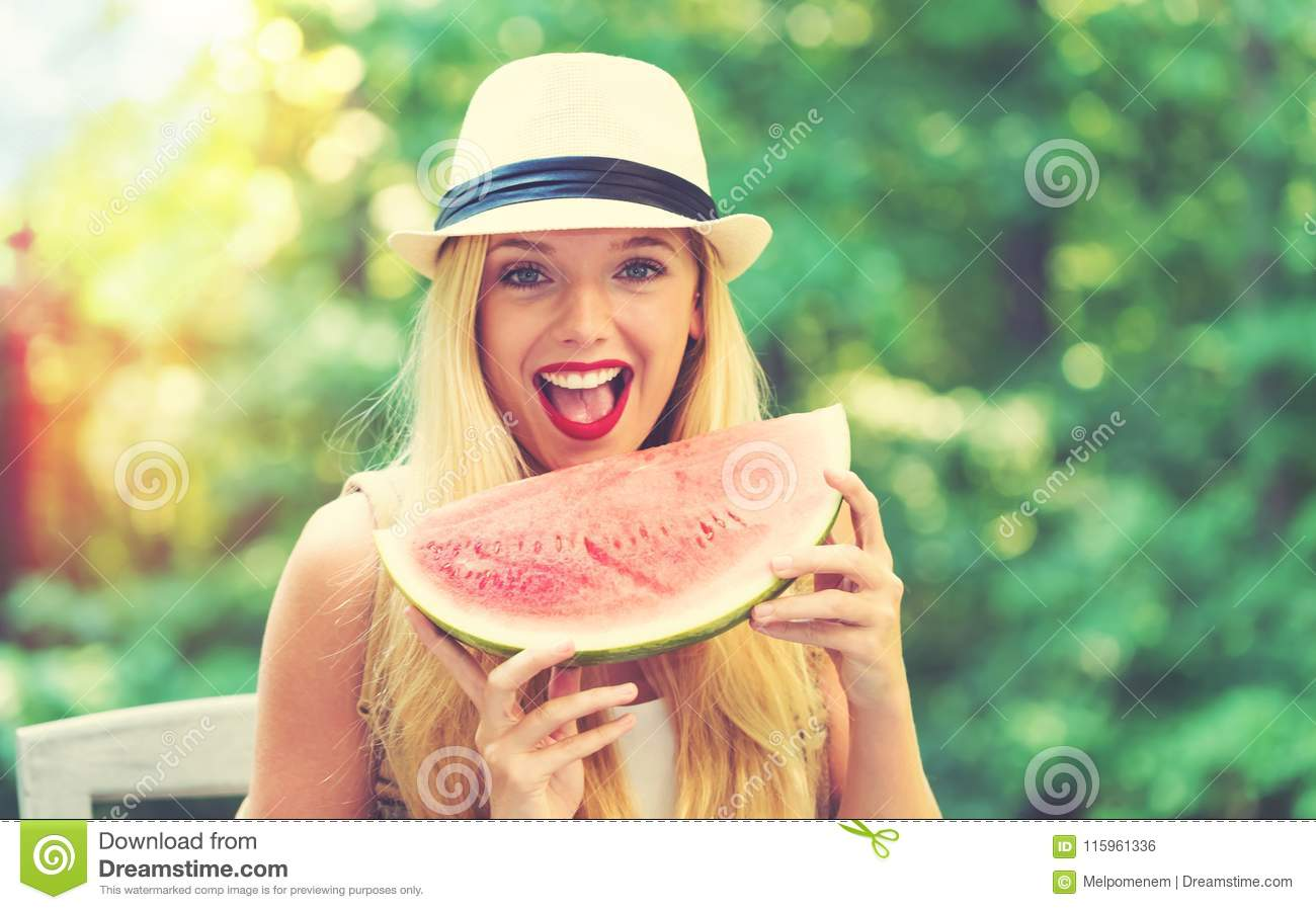Young woman eating watermelon outside
