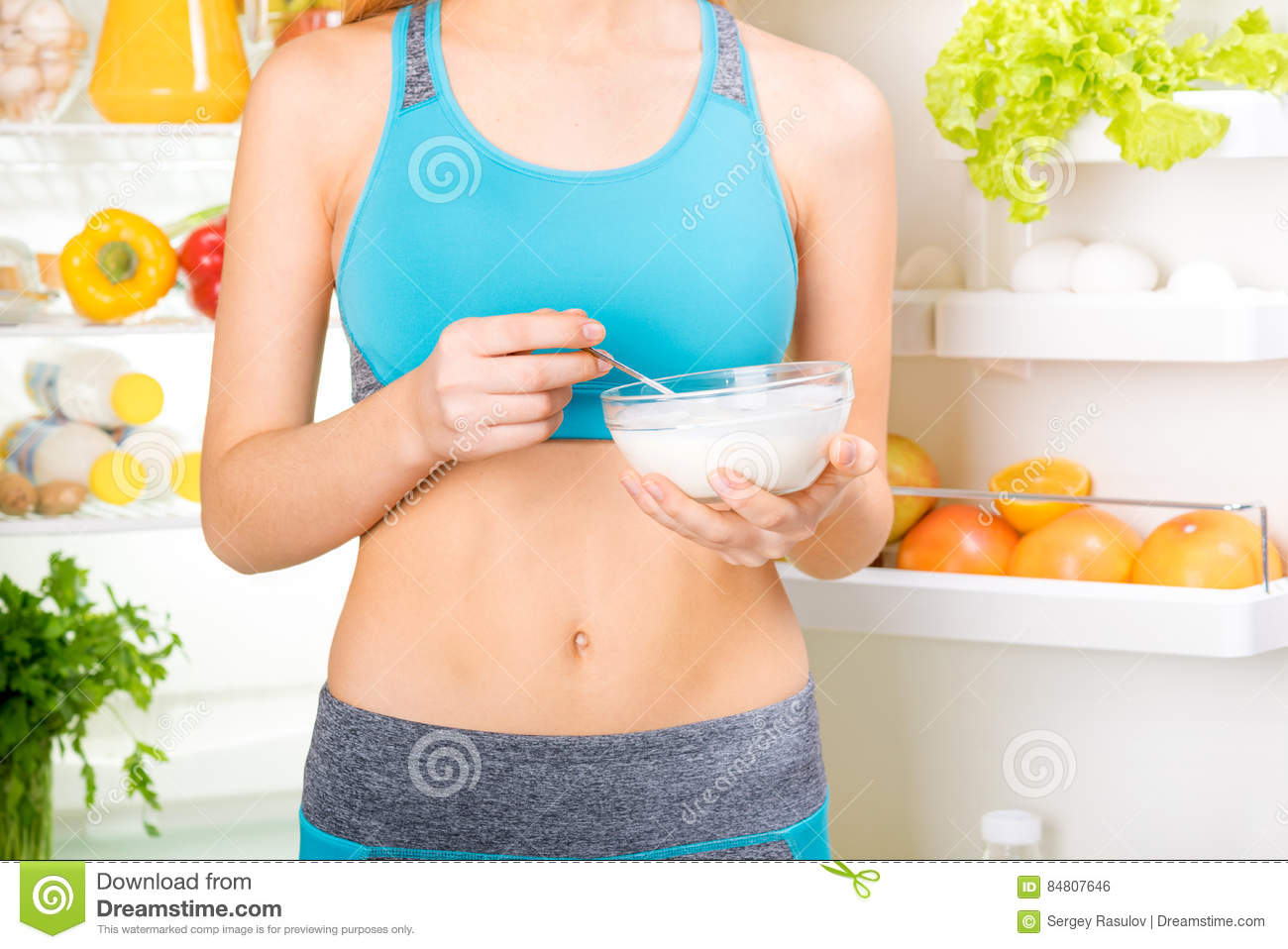Young woman eating a yogurt and staying near the fridge full of health food.