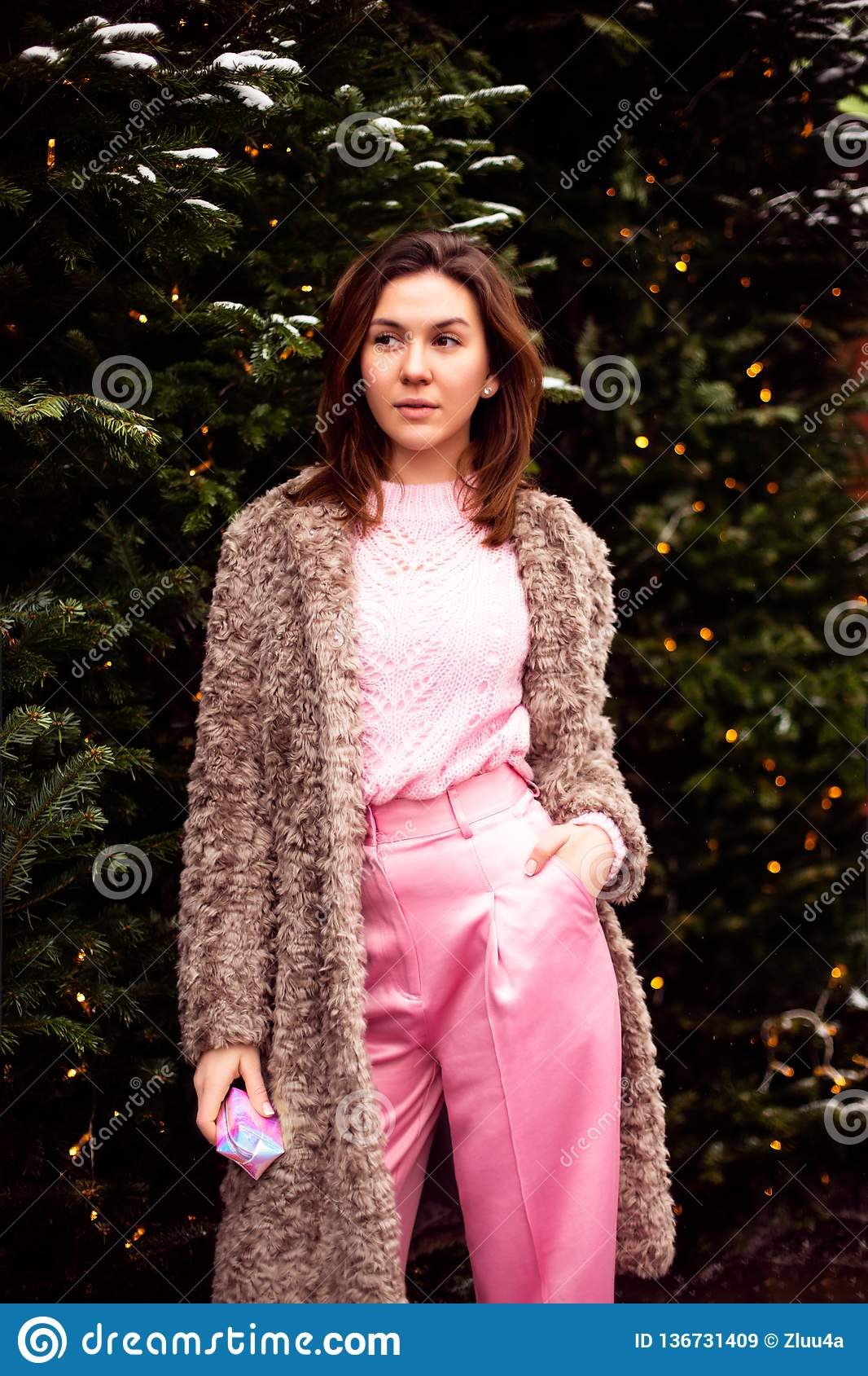 Young woman in eco fur and pink clothes walking on the Christmas decorated street
