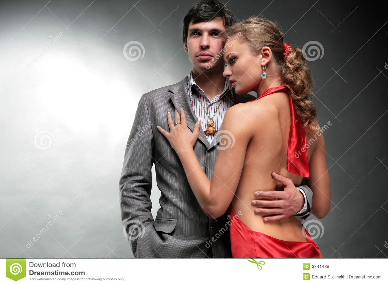 Young woman embraces man. Woman in a red dress.