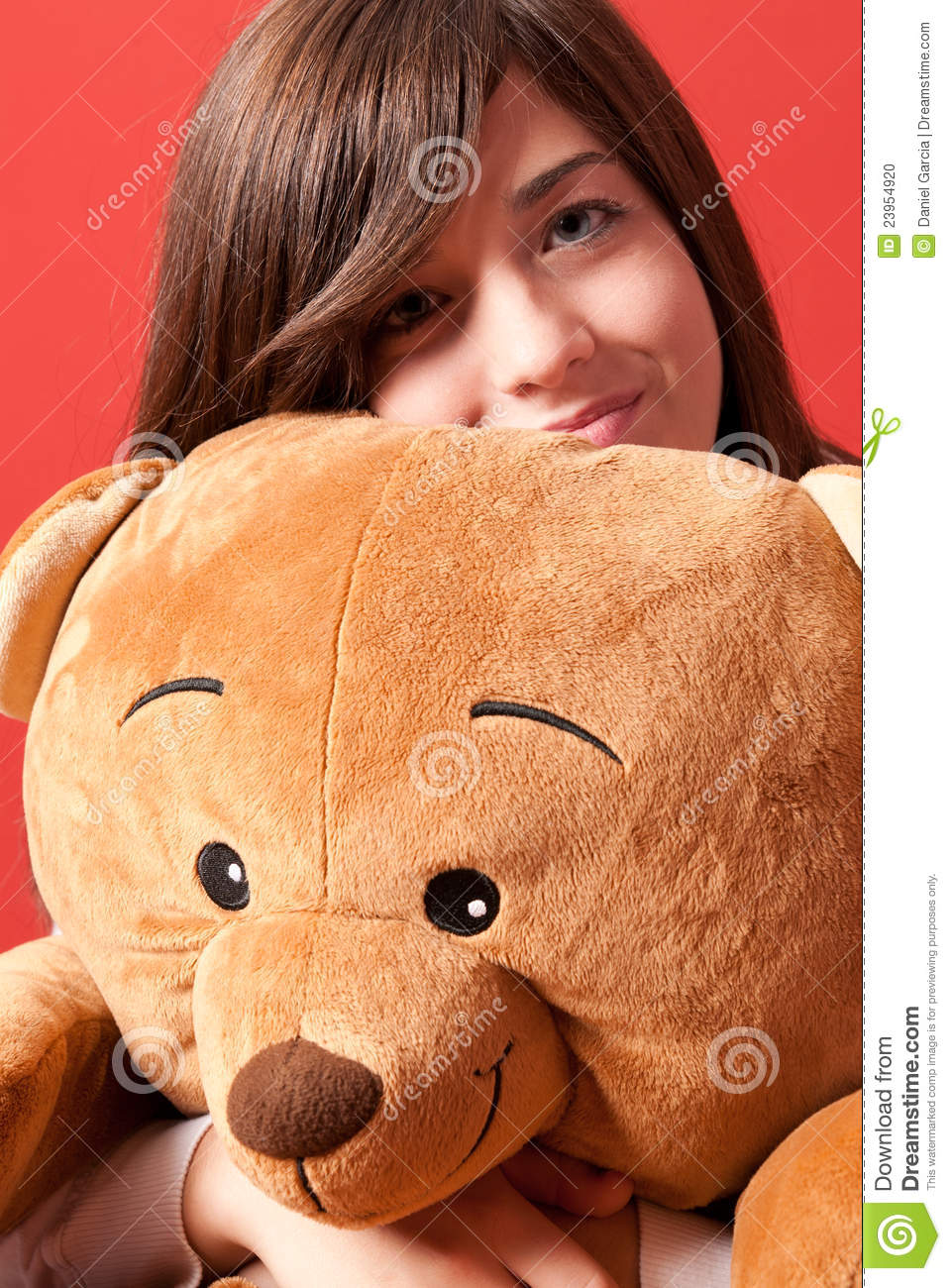 Young woman embracing teddy bear sitting close-up