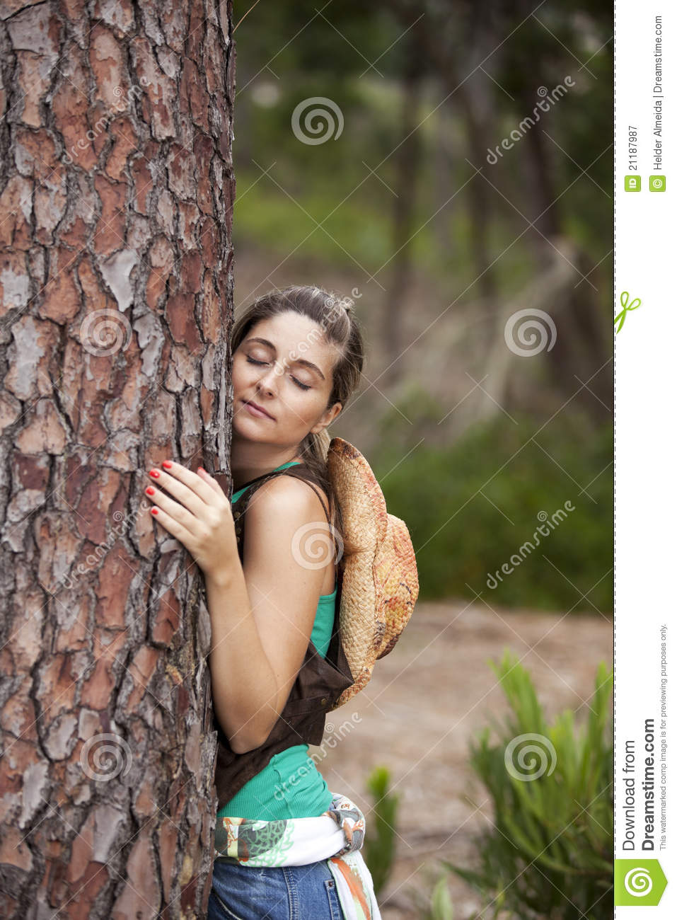 Young woman embracing a tree