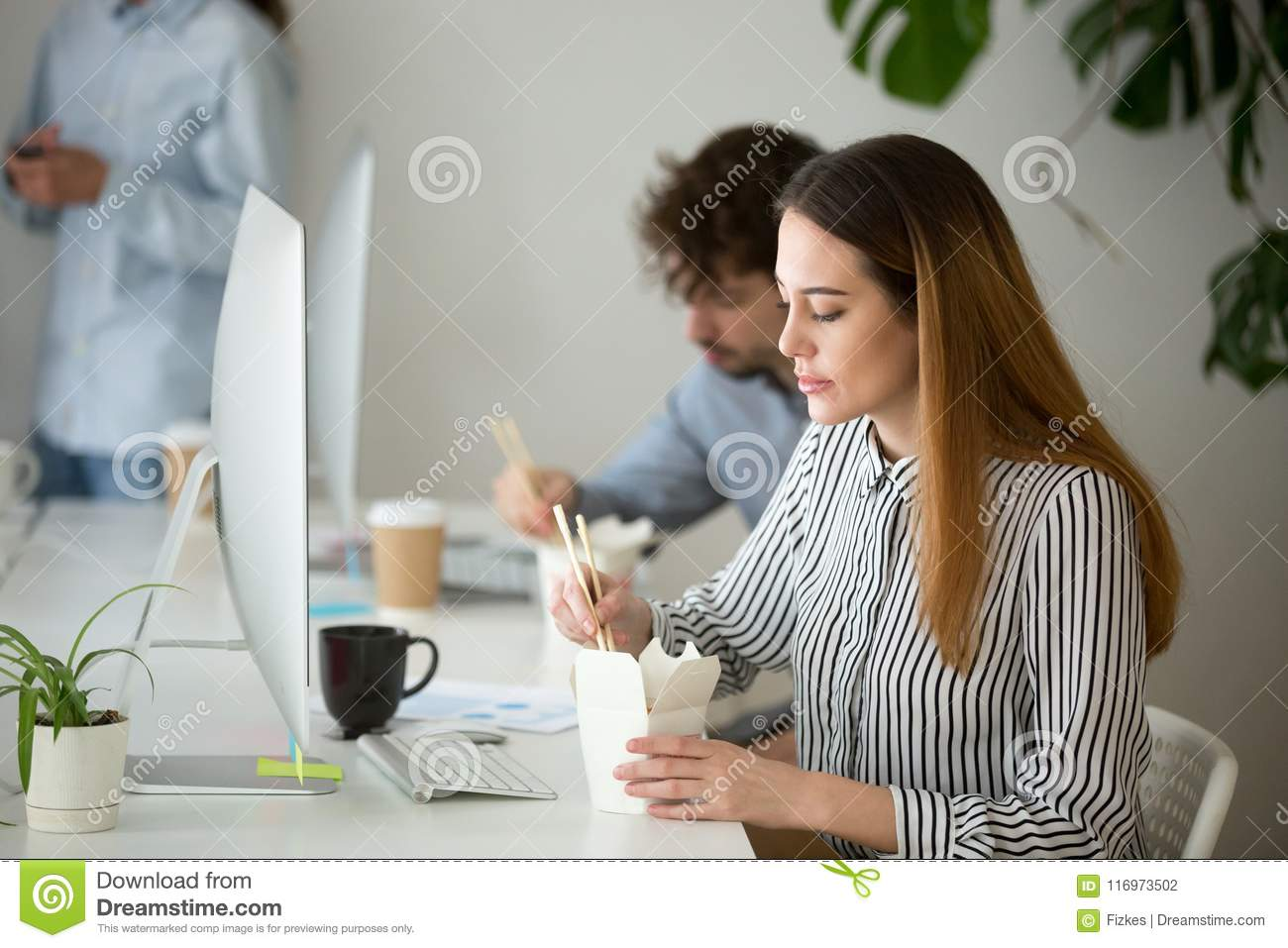 Young woman enjoying chinese food box during office lunch break
