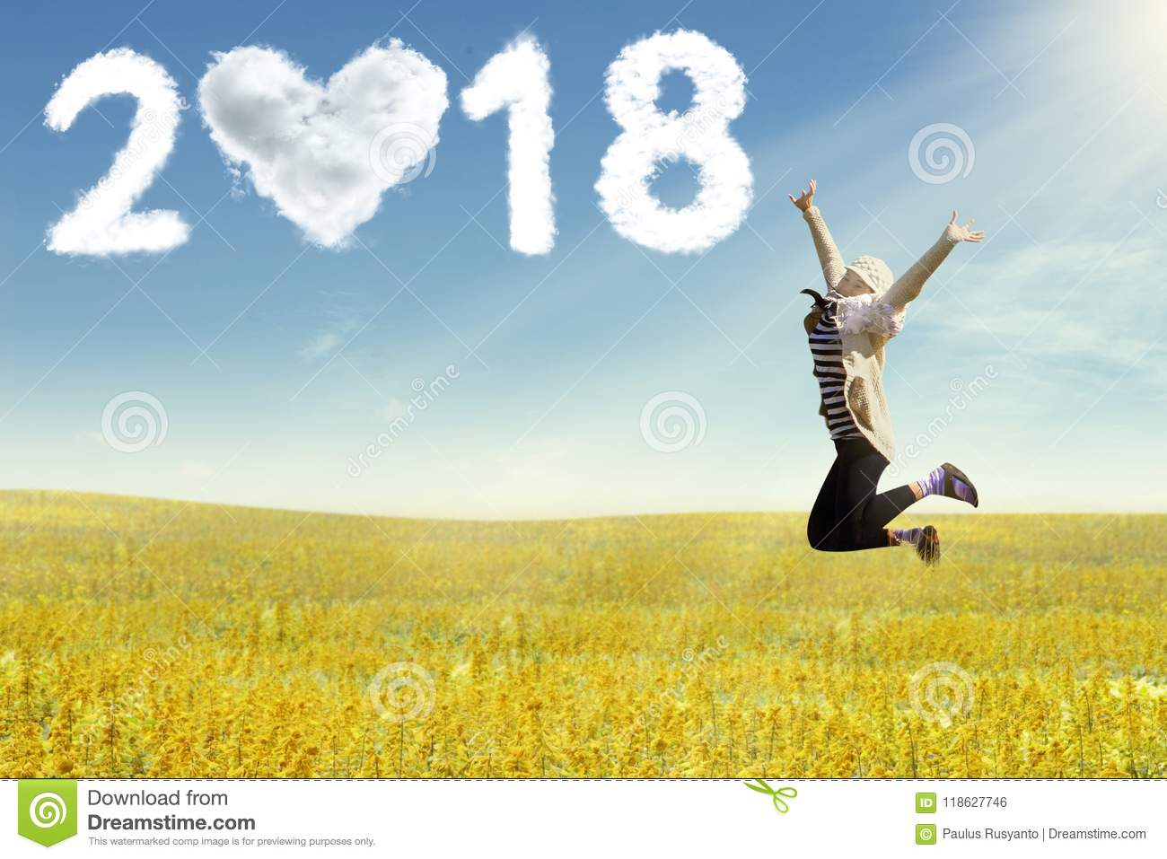 Young woman enjoying the new year jumping on field
