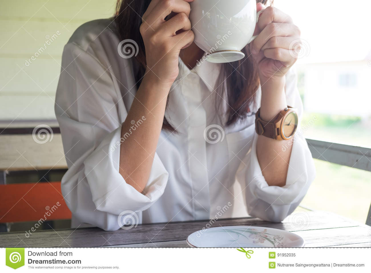 Young woman equip white shirt holding coffee cup and drinking co