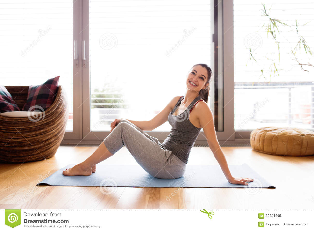 Young woman exercising at home on a mat