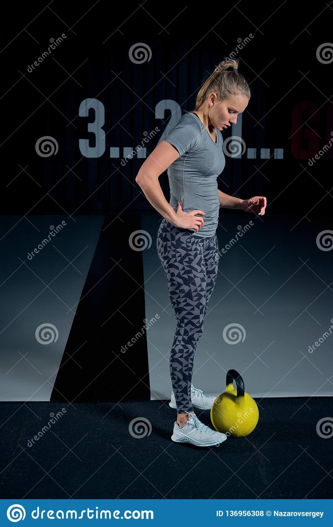 Young woman exercising with kettlebells at the gym squats