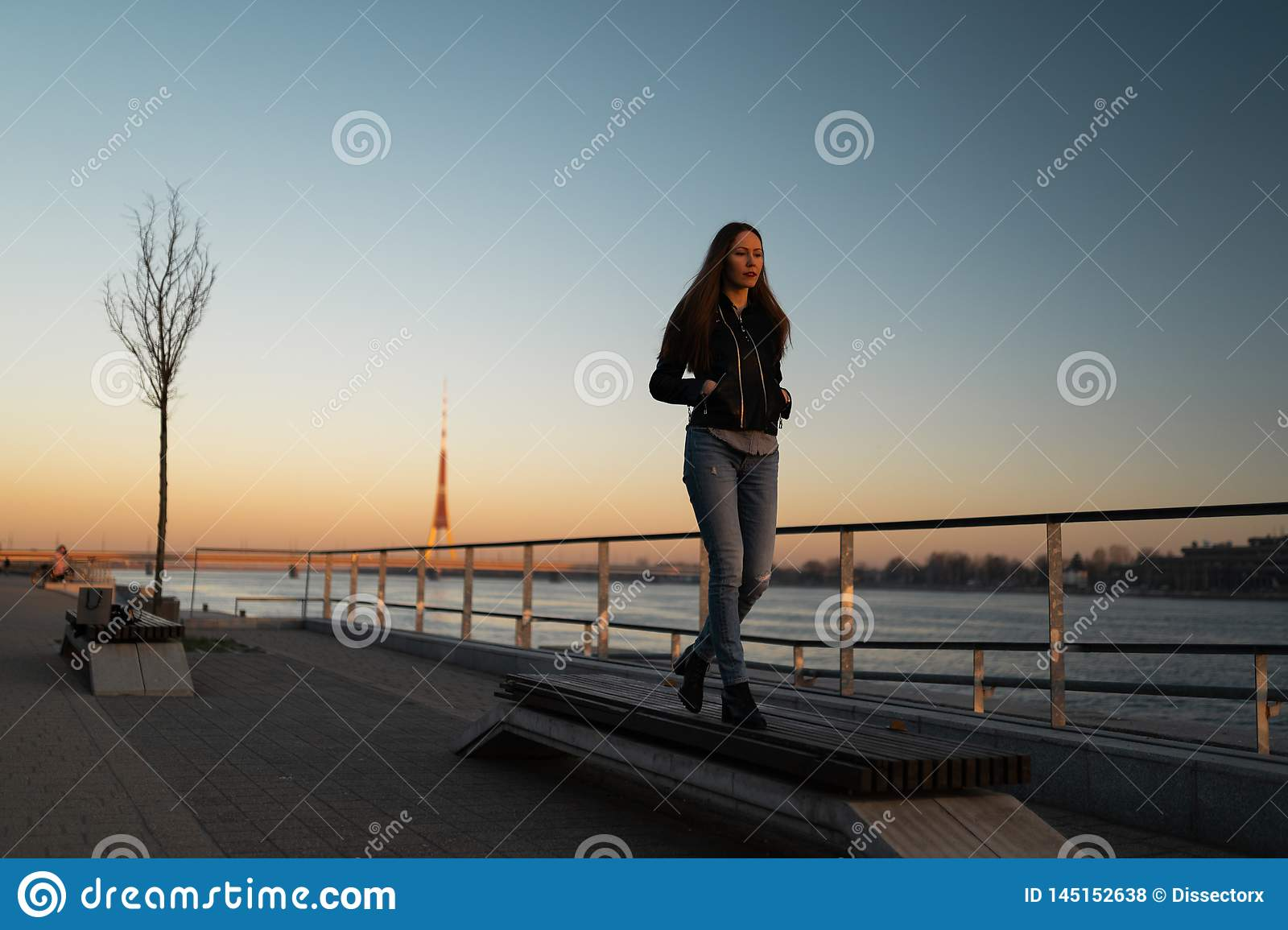 Young woman feeling confident during a lifestyle walk along the River Daugava at a sunset