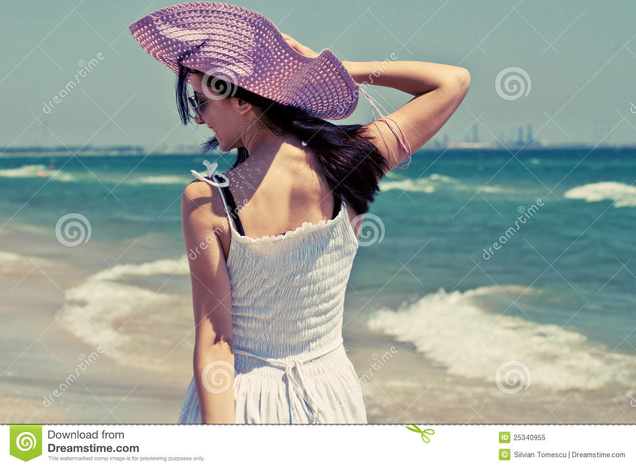 Happy young woman with pink sun hat smiling and walking on the beach