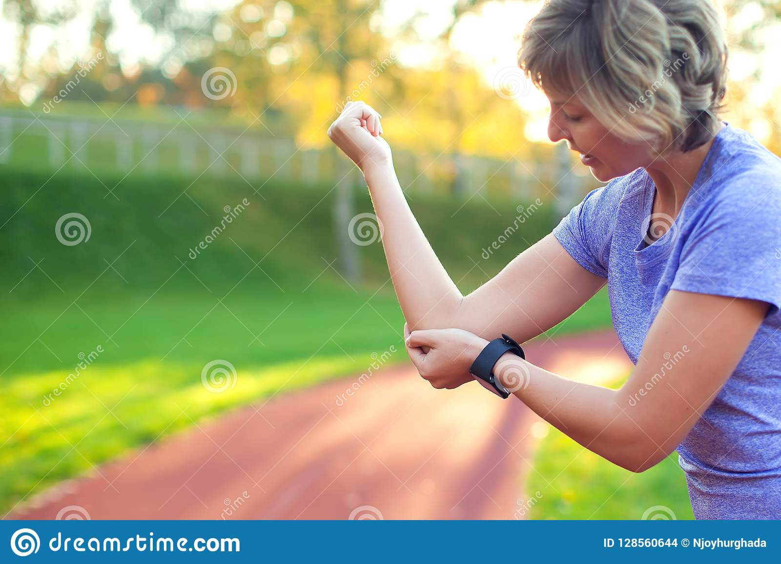 Young woman feeling pain in her elbow during sport workout at st