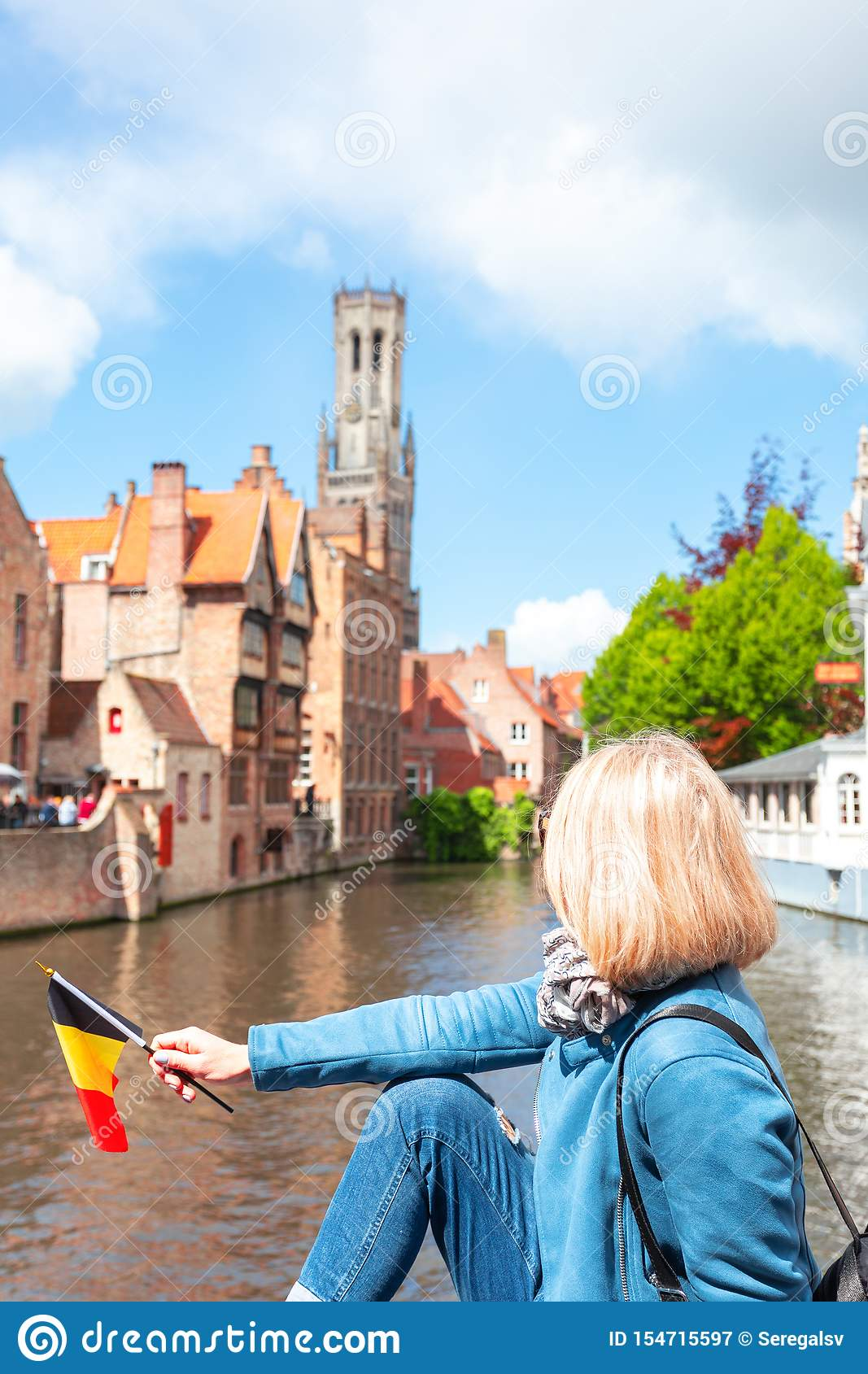 A young woman with the flag of Belgium in her hands is enjoying the view of the canals in the historical center of