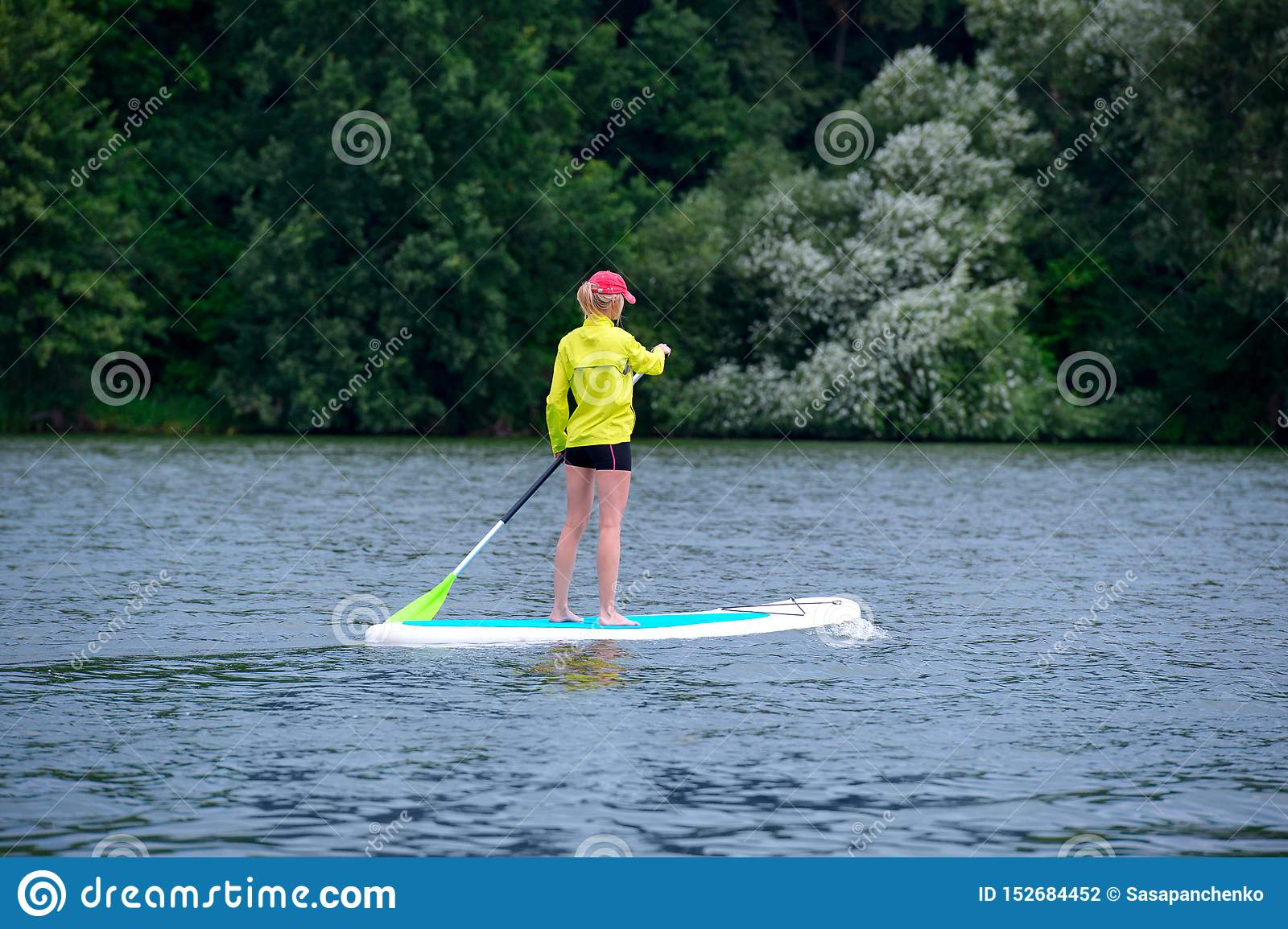 A young woman floats on a SUP board along a large river. Swim on the board for amazing outdoor activities