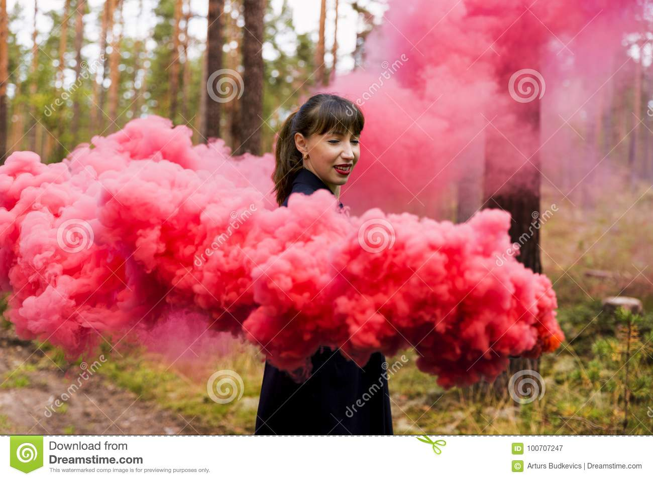 Young Woman In Forest Having Fun With Red Smoke Grenade