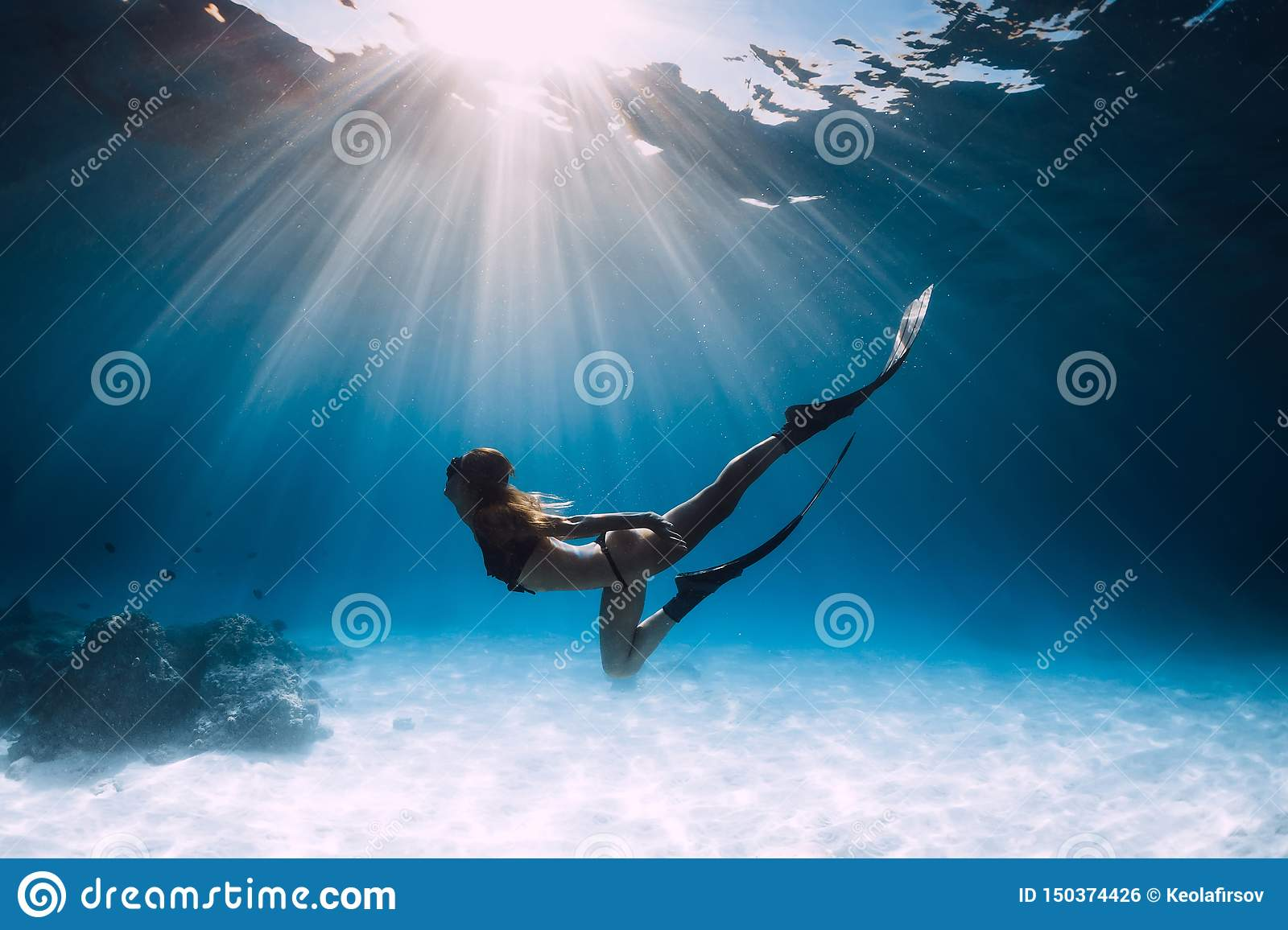 Young woman freediver glides over sandy sea