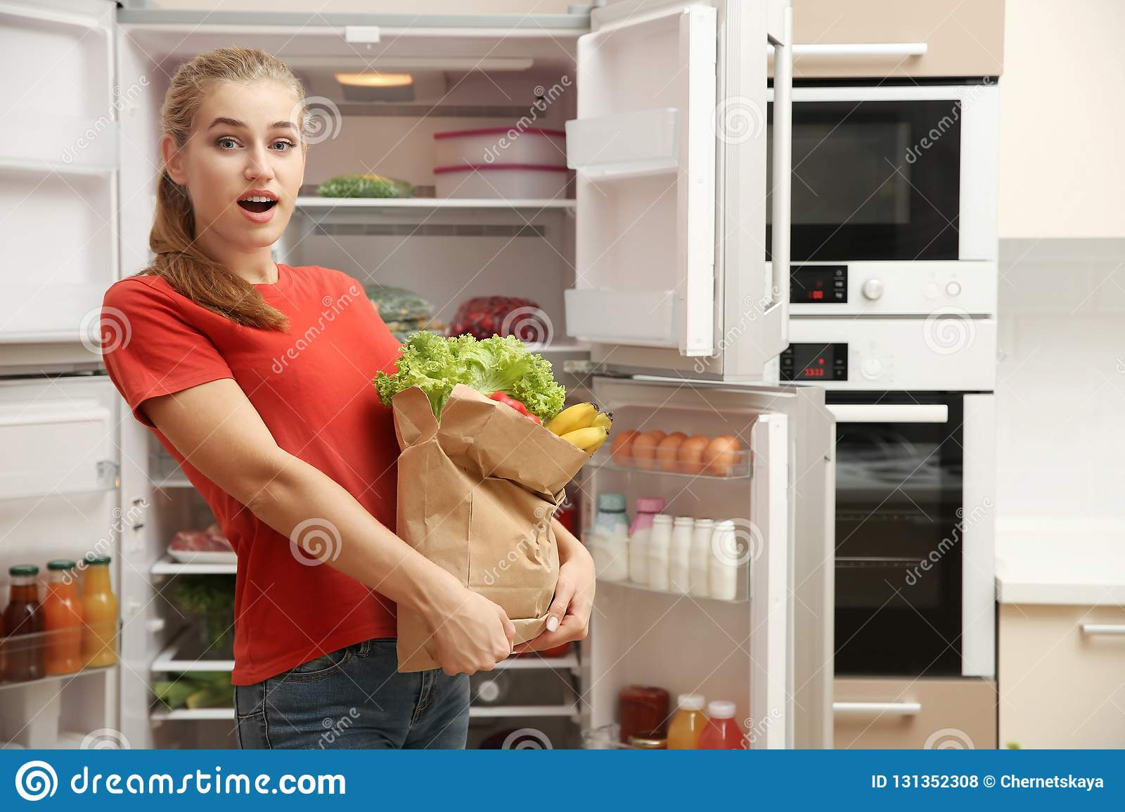 Young woman with fresh food in paper bag near refrigerator