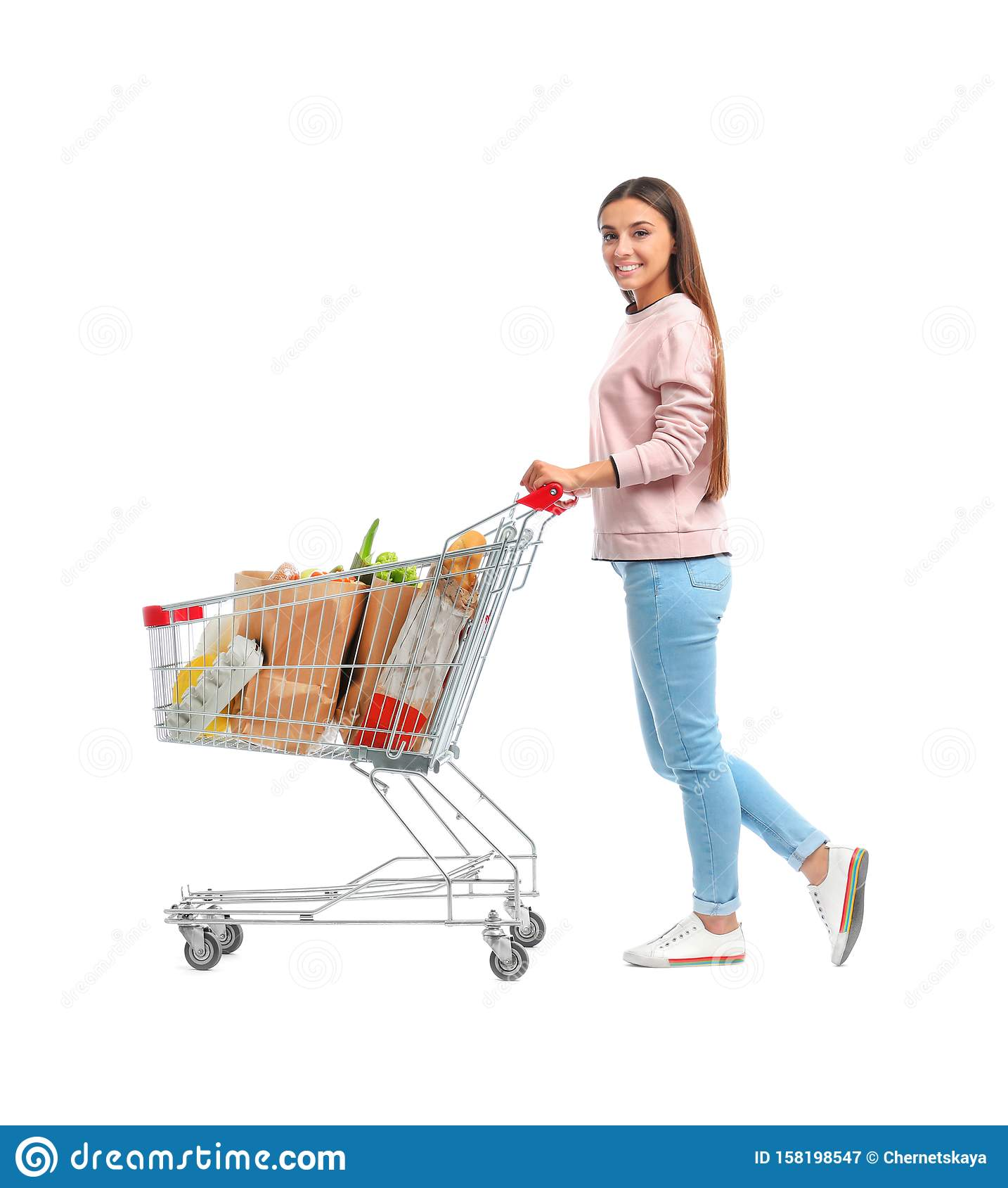 Young woman with full shopping cart on background