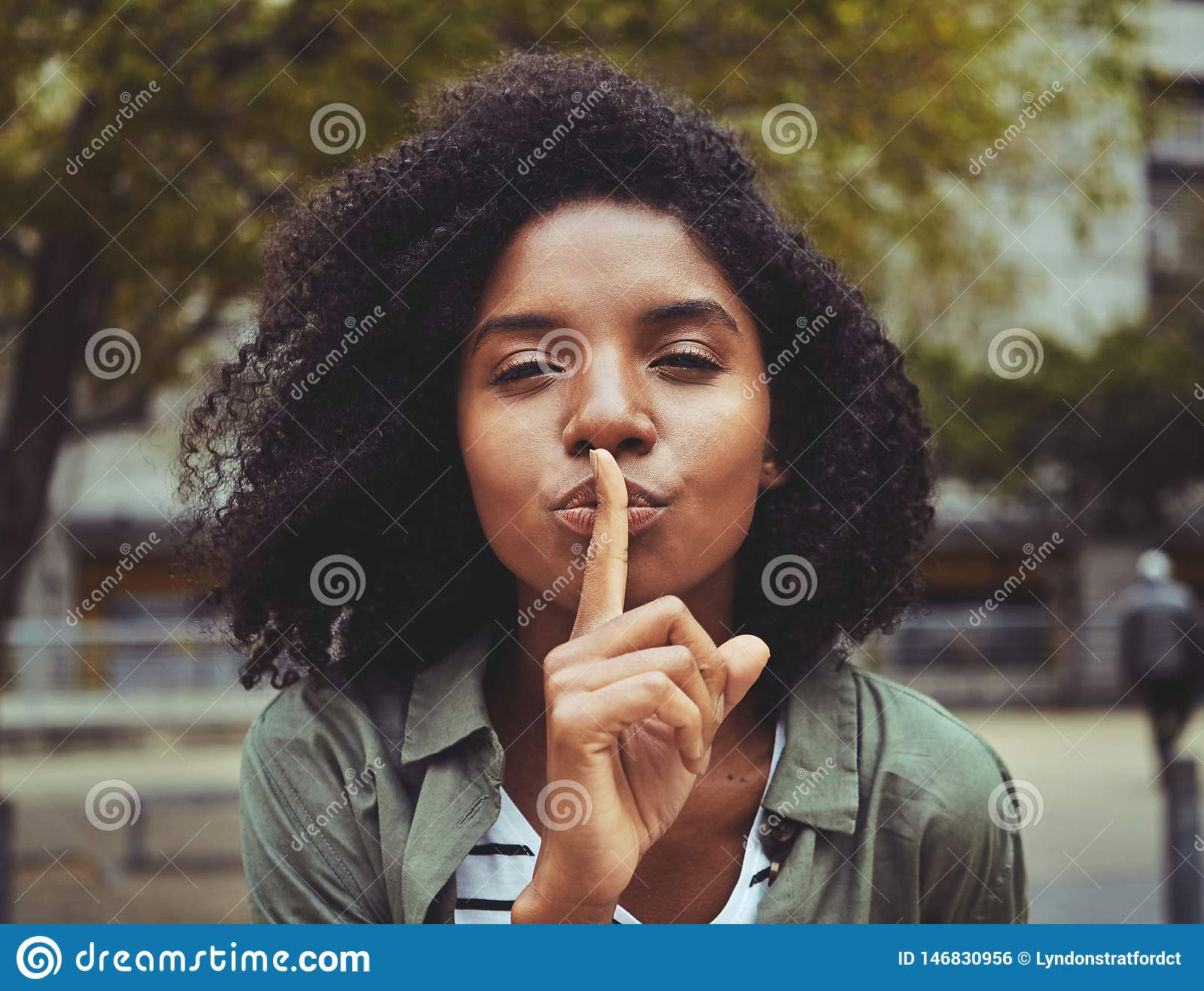 A young woman gesturing silence sign