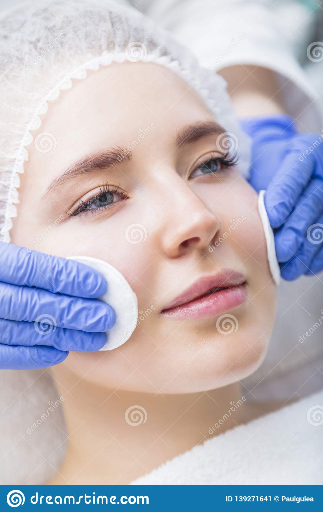 Young woman getting face procedure at salon
