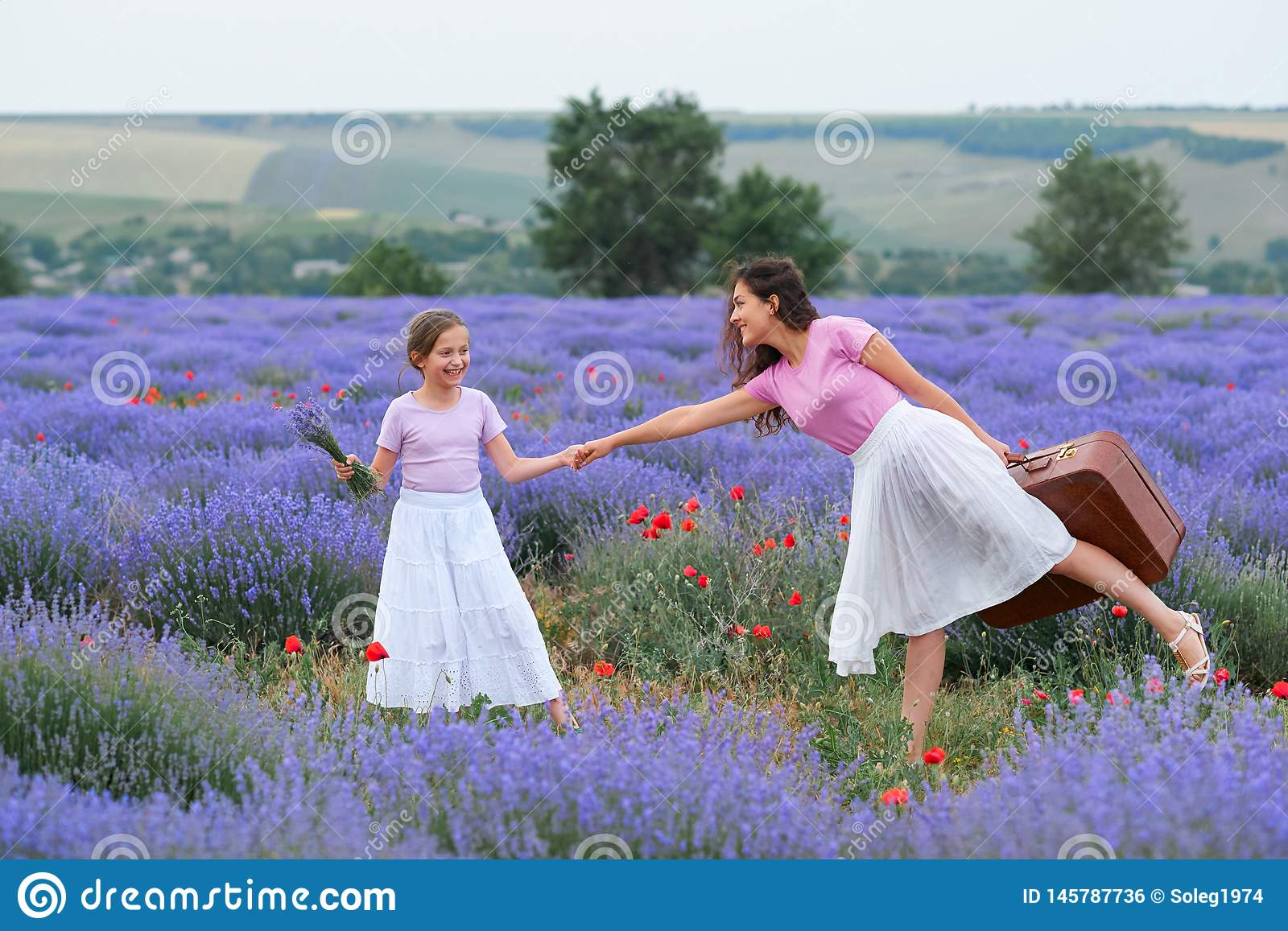 Young woman and girl are walking through the lavender flower field, beautiful summer landscape