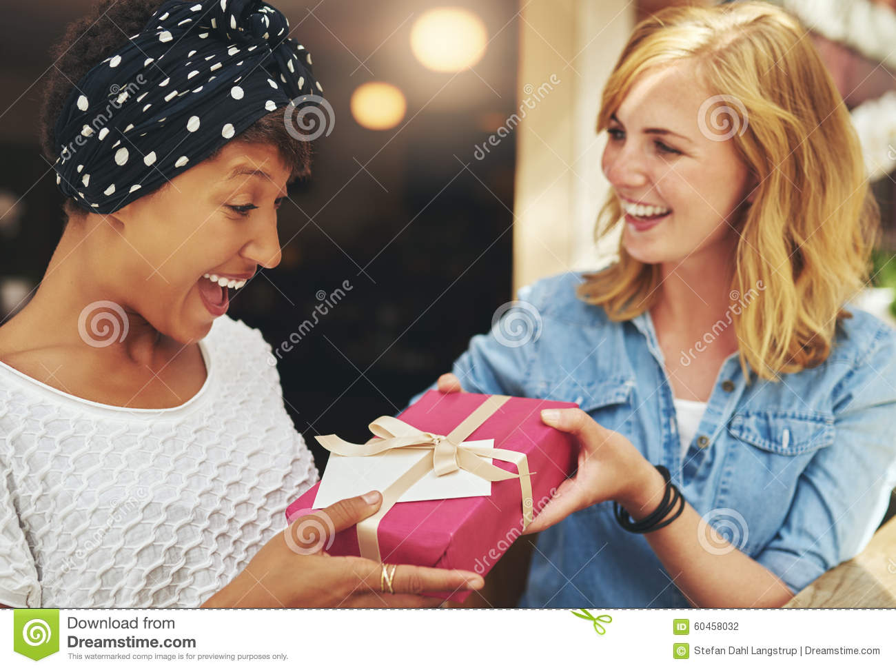 Young woman giving a friend a surprise gift