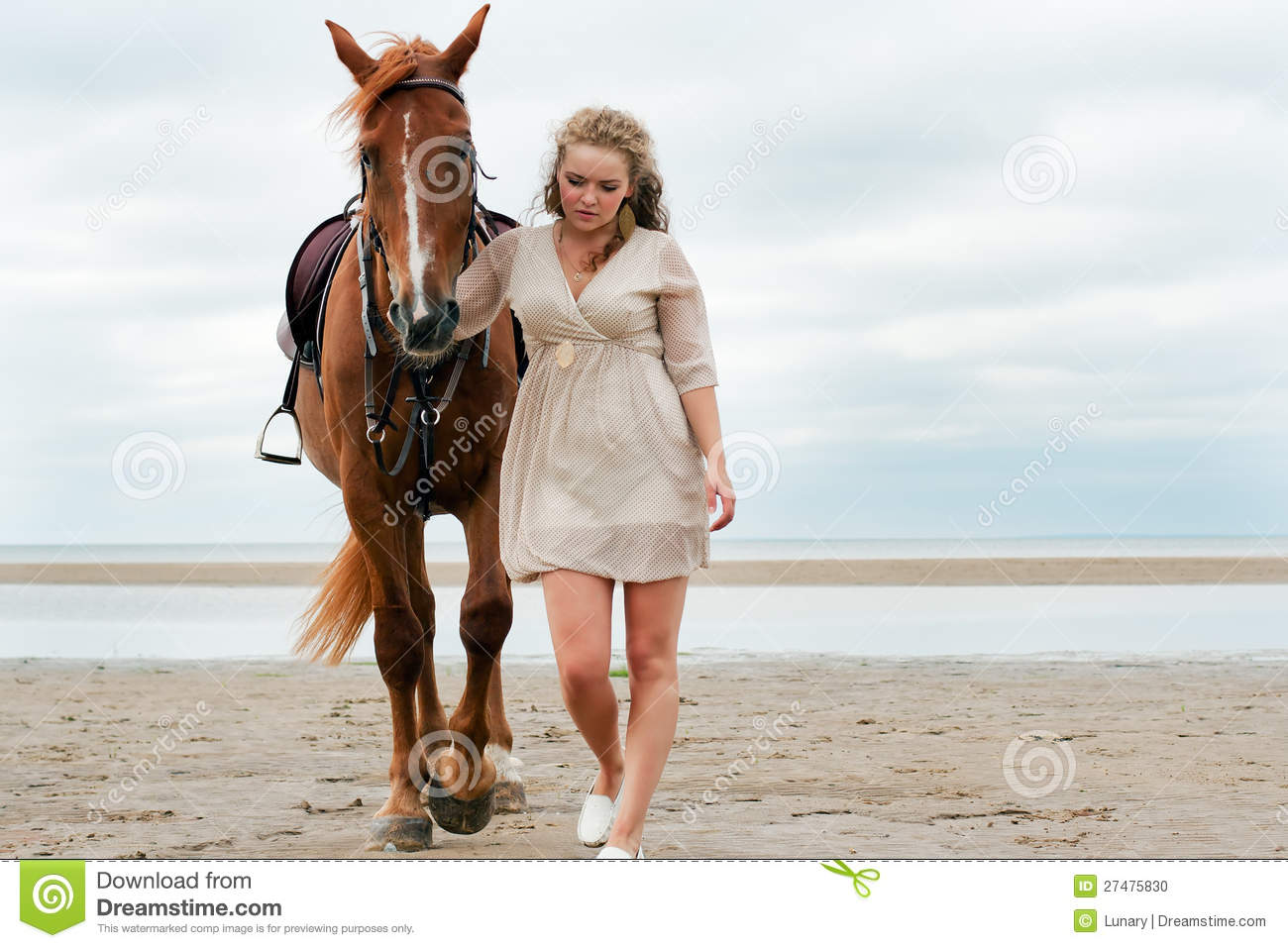 Young woman goes near a horse