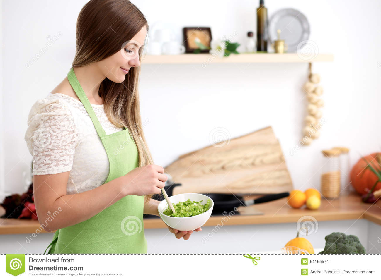 Young Woman In The Green Apron Cooking In The Kitchen. Housewife ...