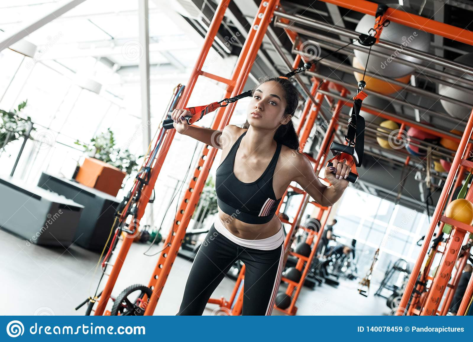 Young woman in gym sporty lifestyle total resistance workout doing back exercise with suspansion straps