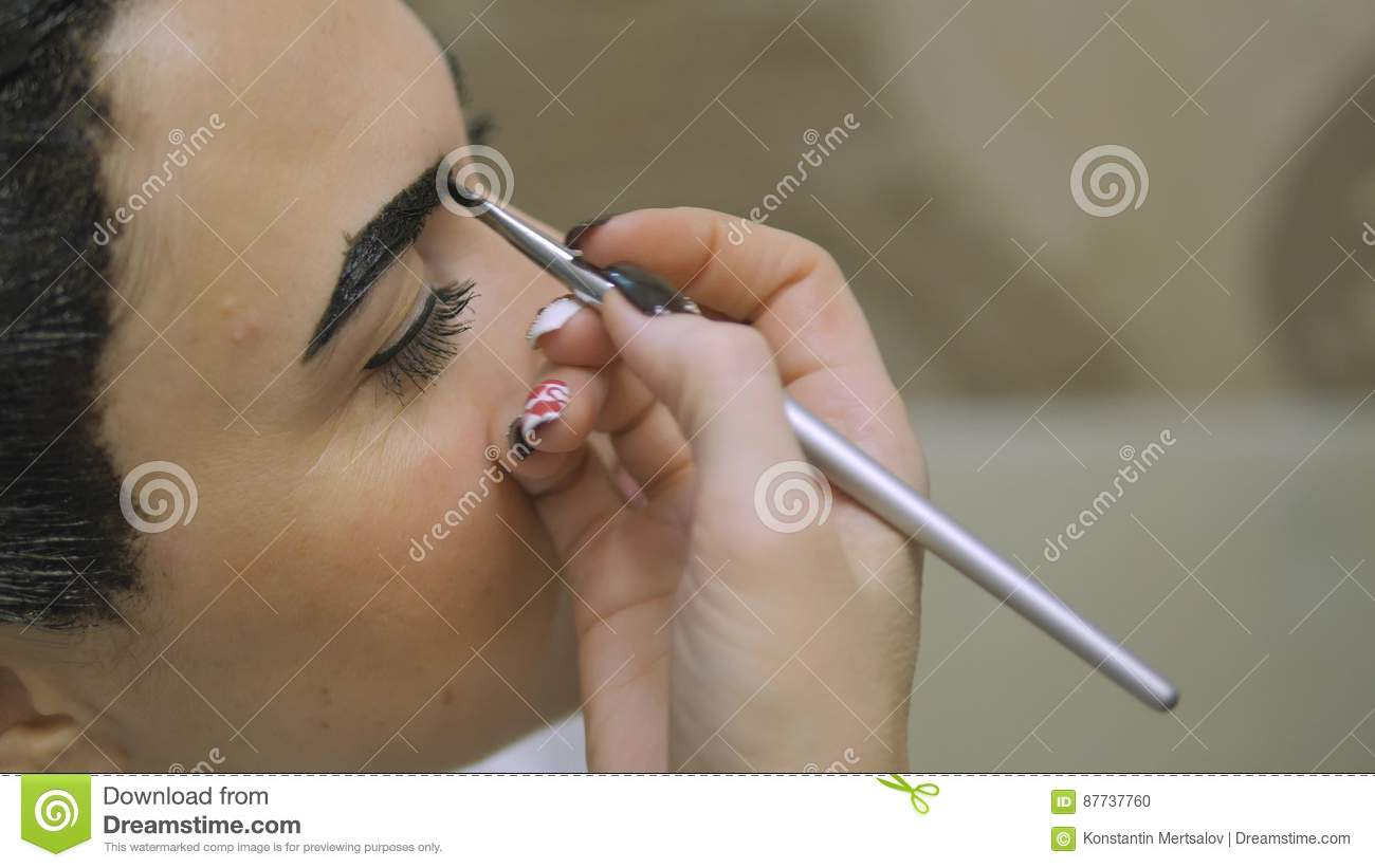 Young Woman With Hair In The Paint To Eyebrow Make Up Sitting From