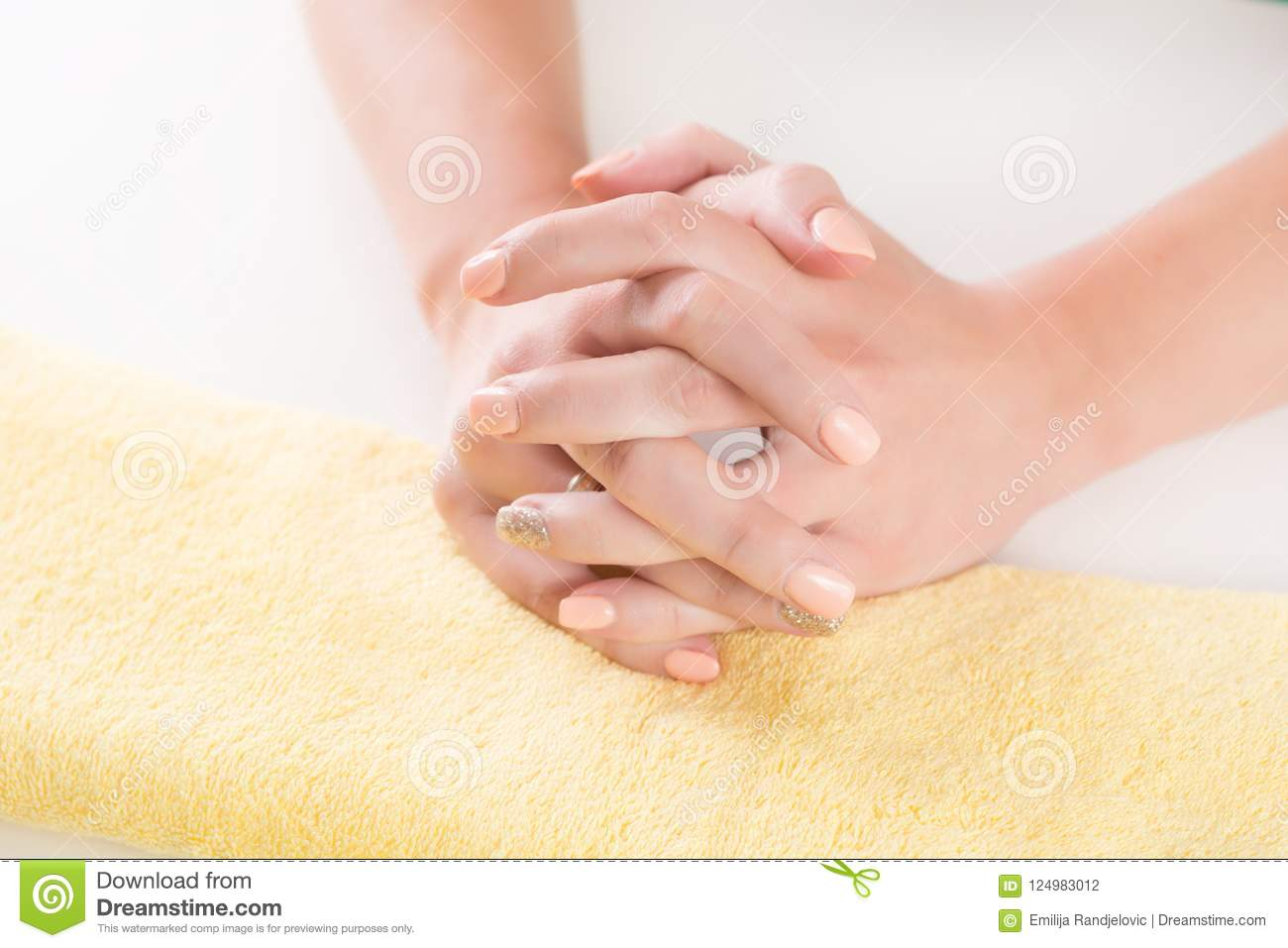 Young woman hand with orange manicure