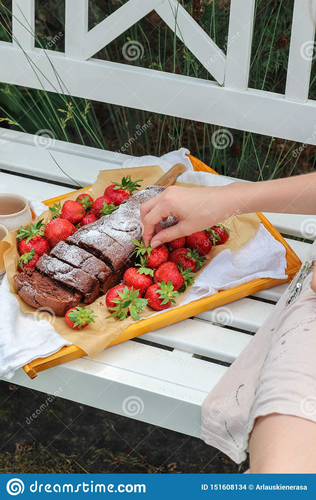 Young woman hand reaching for a tray with homemade cake and fresh strawberries