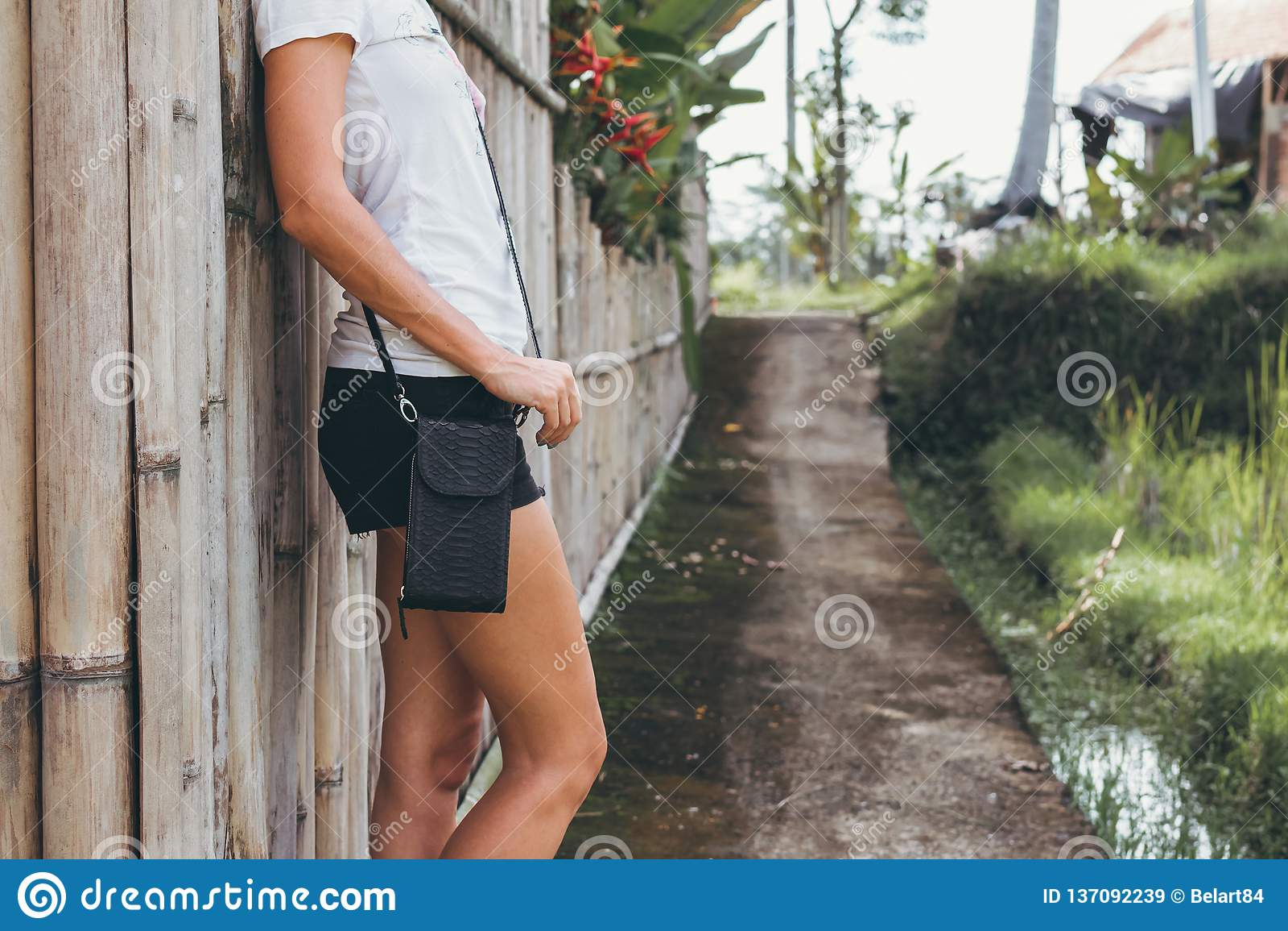 Young woman hands with stylish luxury snakeskin python handbag outdoors. Bali island.