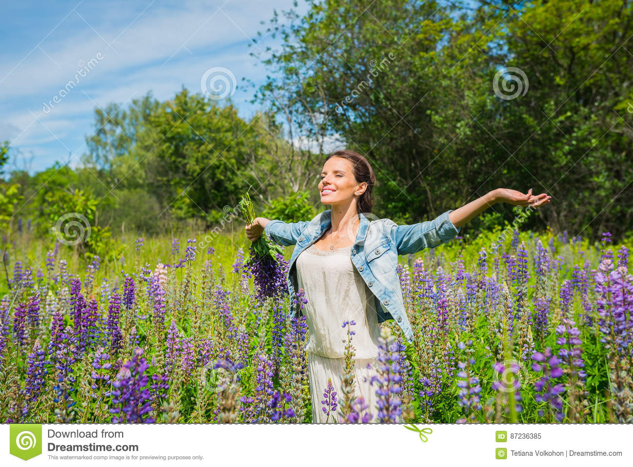 Young woman, happy, standing among the field of violet lupines, smiling, purple flowers. Blue sky on the background. Summer, with