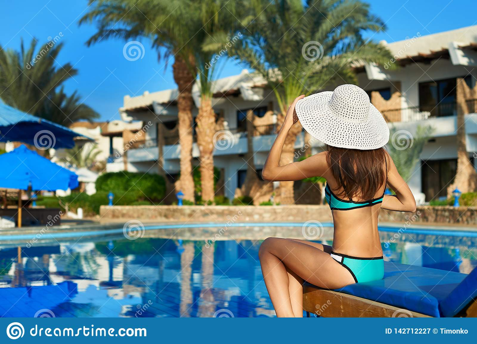 Young woman in hat sitting on a sun lounger near swimming pool, concept time to travel. Relax in the pool summer