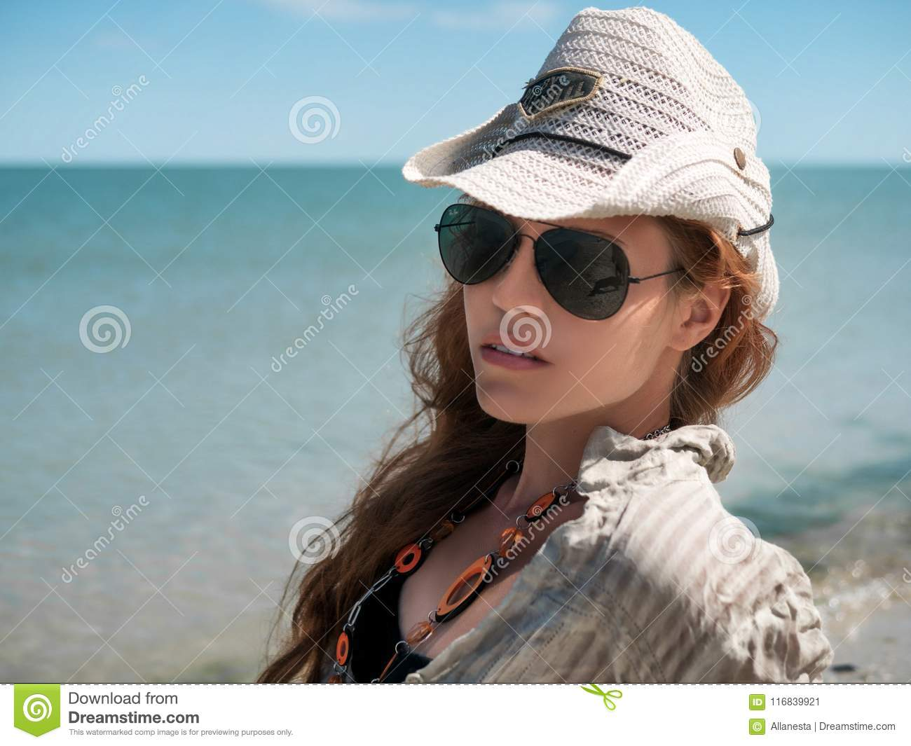 Young woman in hat, sunglasses and shirt sits at the seaside of the ocean, sea at sunny day Beautiful Woman Laughing On Summer Tra