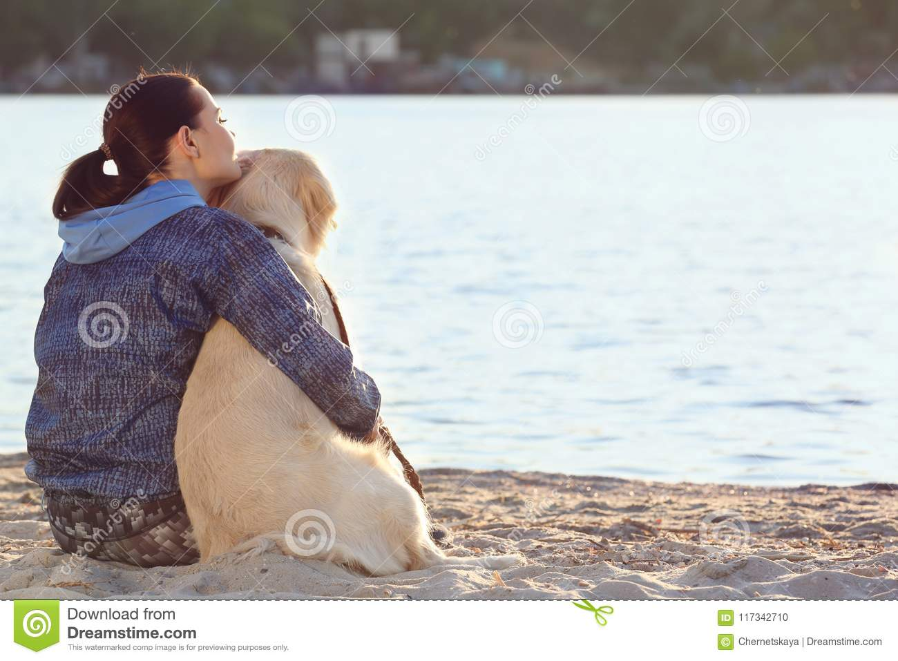 Young woman with her dog together on beach