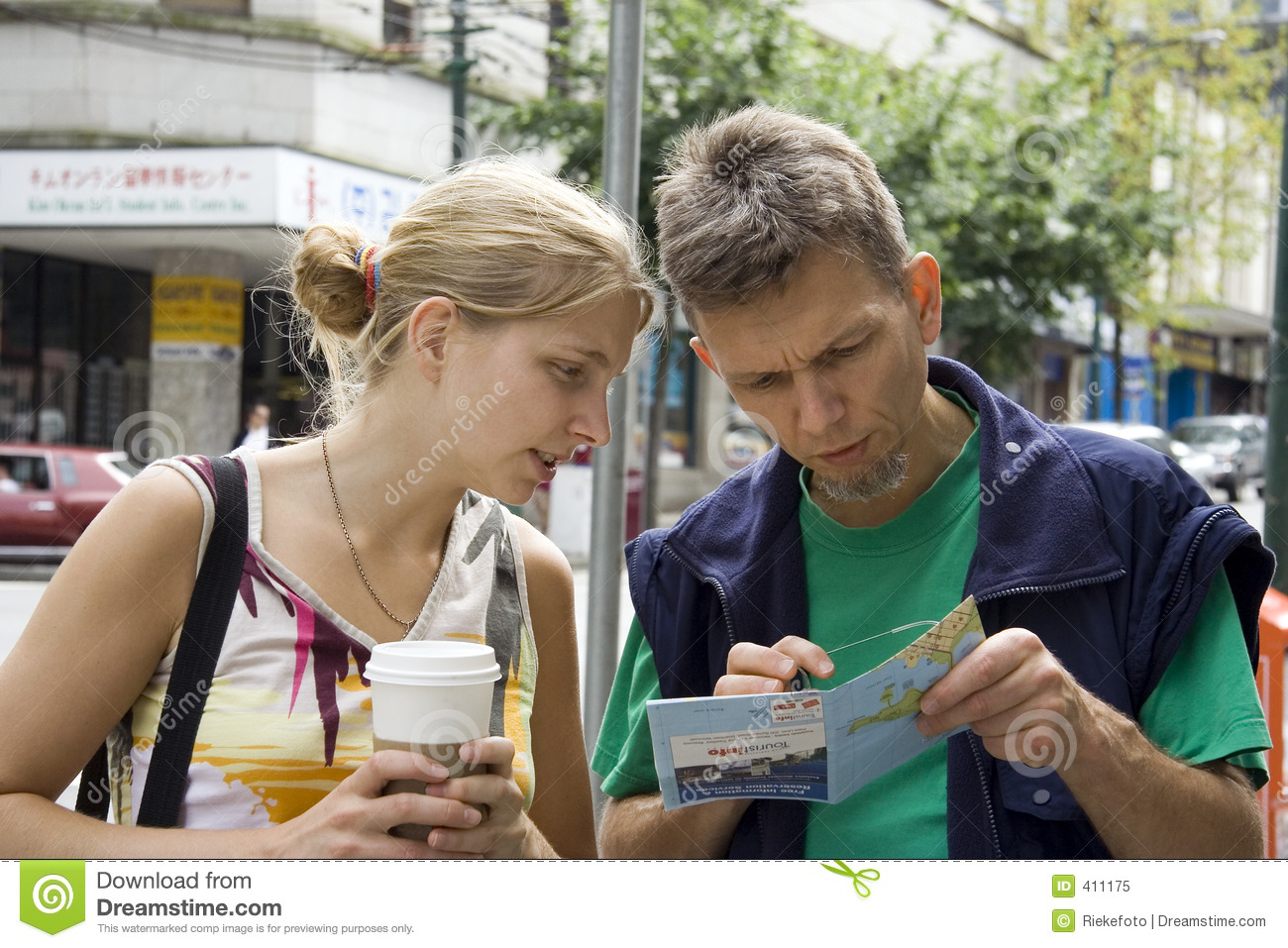 Young woman and her father studying a city map