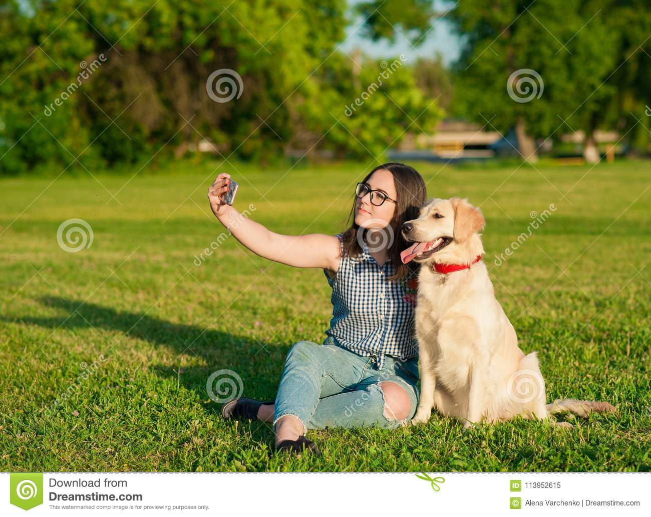 Young woman and her friendly dog taking a selfie at a park