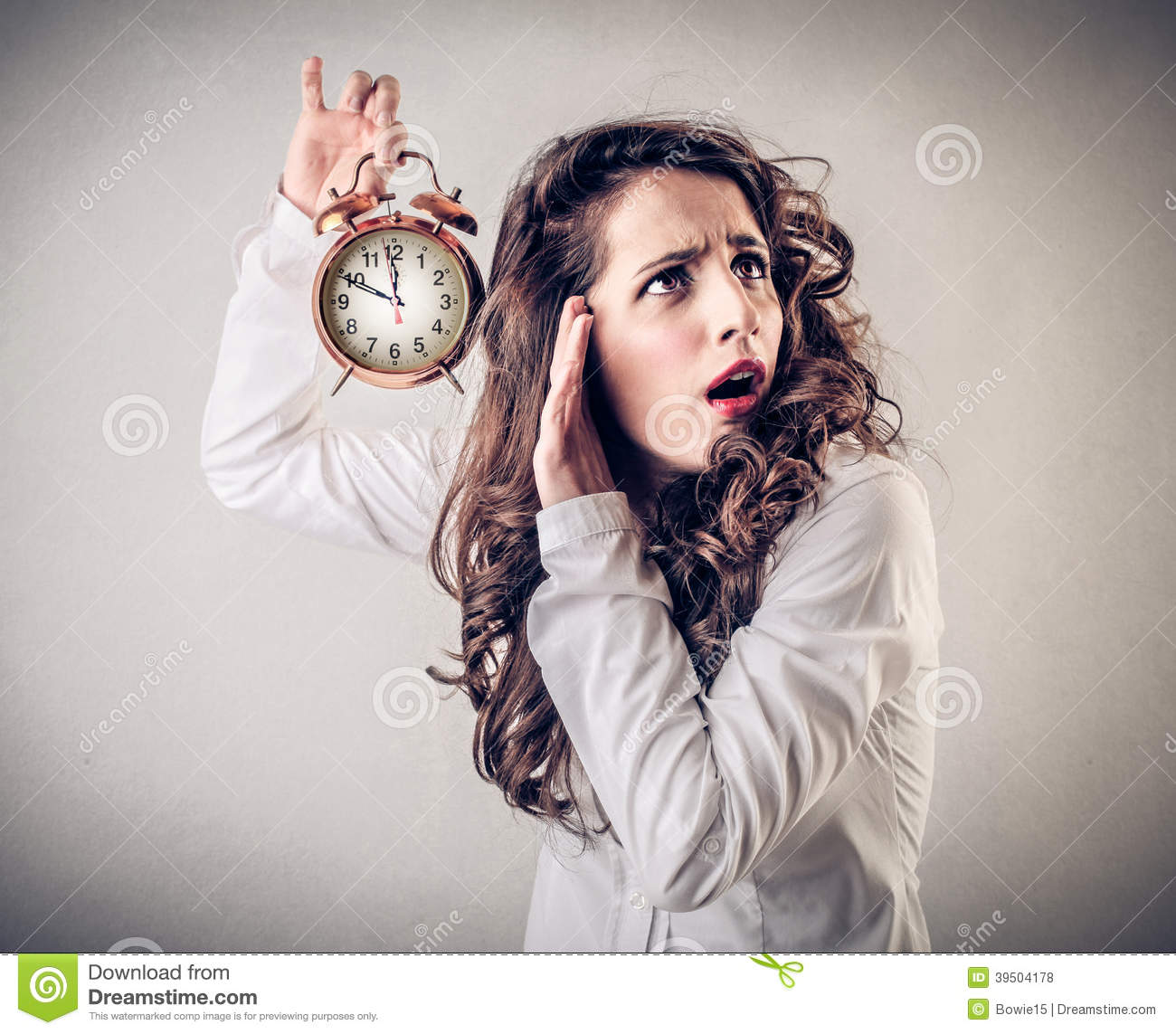 Young woman holding an alarm clock