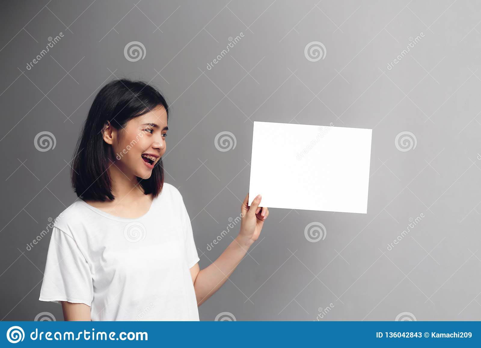 Young woman holding a blank poster for text on a white background
